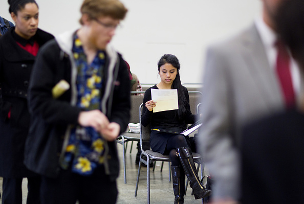 A job seeker looks over paperwork during a Choice Career Fair event in Seattle, Washington, U.S., on Thursday, Jan. 28, 2016. Applications for unemployment benefits in the U.S. declined last week from a six-month high, indicating firings remain low following the volatility typically associated with post-holiday staff adjustments. Photographer: Mike Kane/Bloomberg via Getty Images