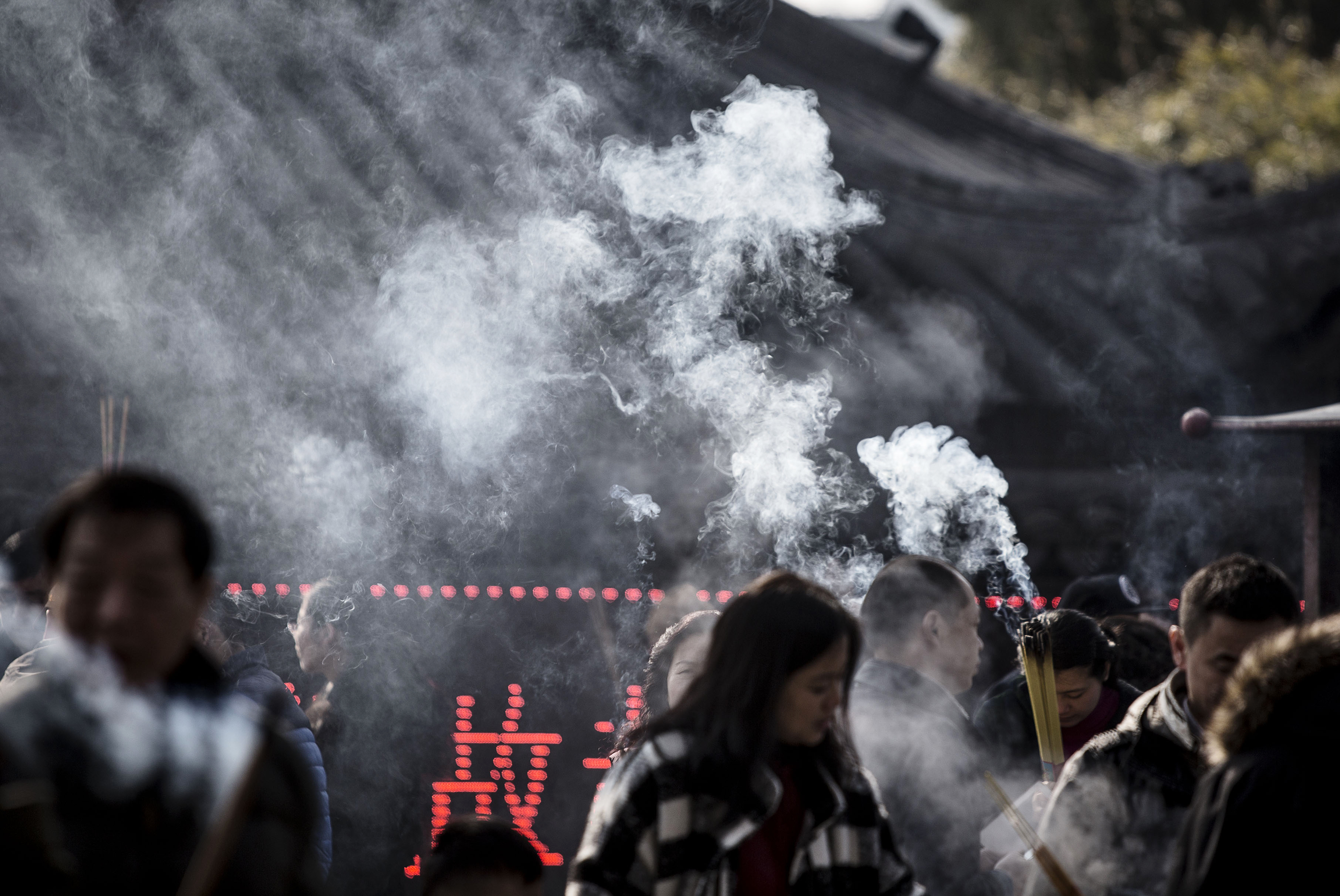 Worshipers pray and make offerings of incense sticks at Longhua Temple in Shanghai, China, on Tuesday, Feb. 9, 2016.
