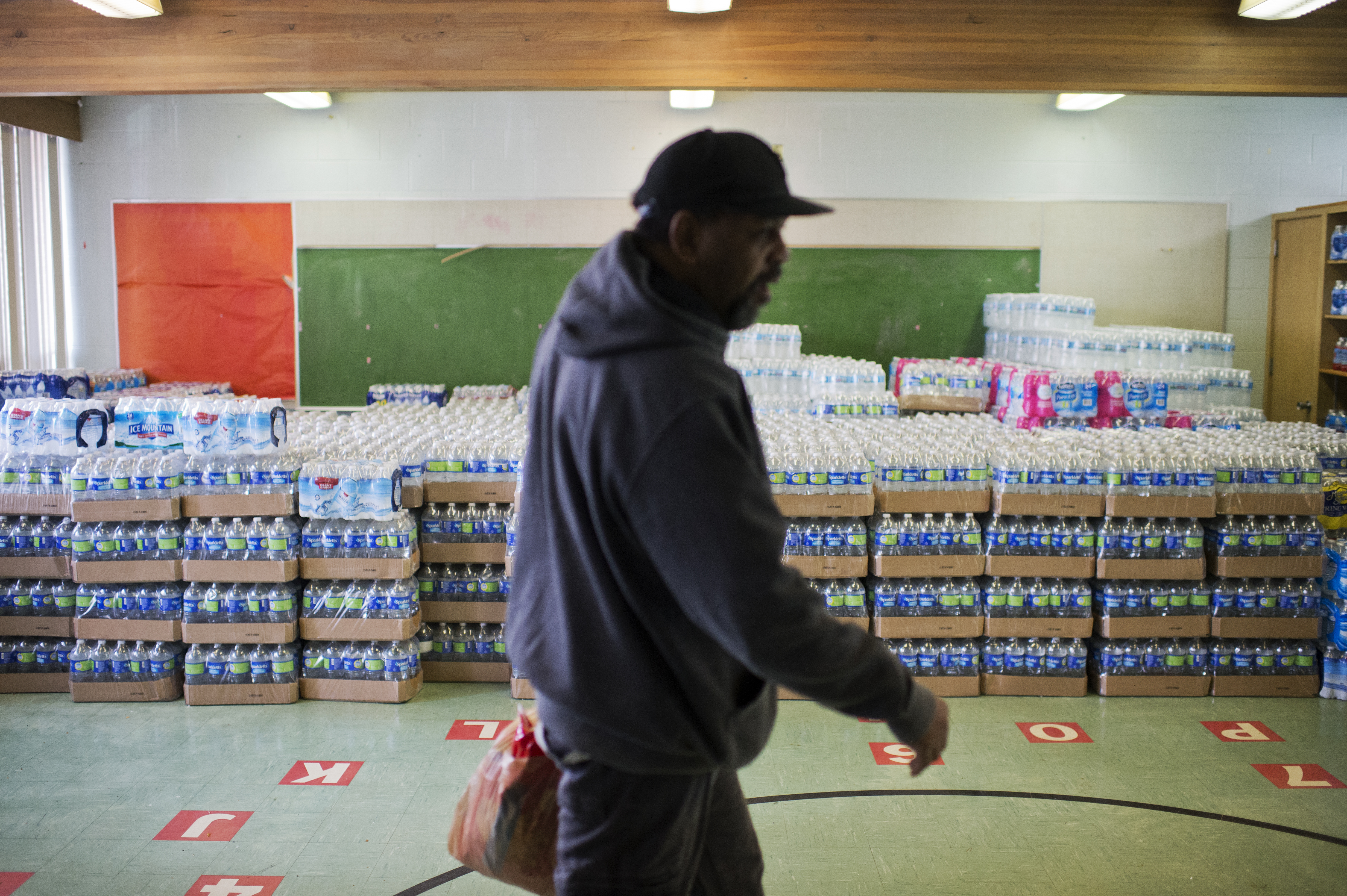 A volunteer walks by cases of bottled water at the St. Mark Baptist Church, that serves as a water distribution area in Flint, Mich., on Feb. 23, 2016.