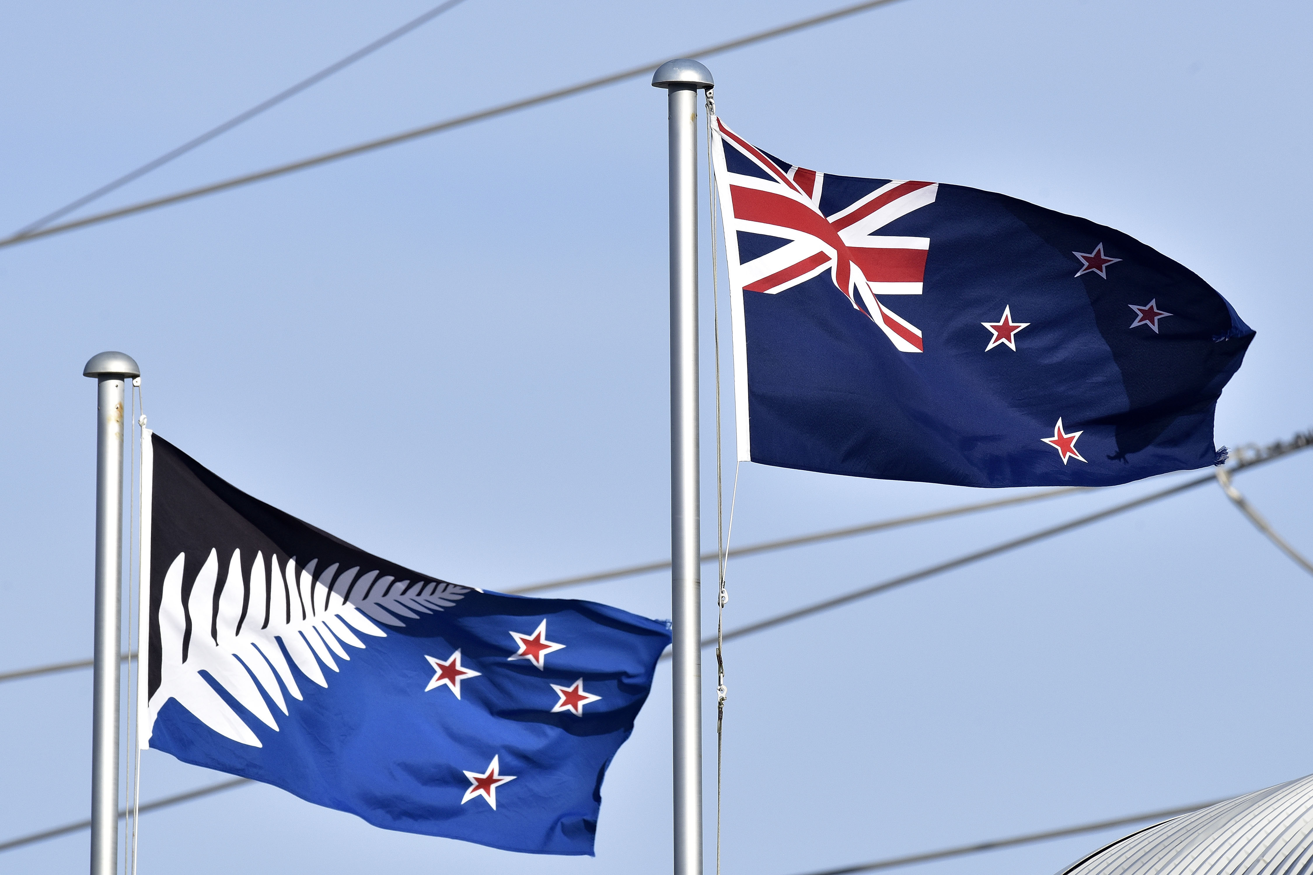 The current New Zealand flag, right, flutters next to the proposed new flag in Wellington, New Zealand, March 4, 2016.