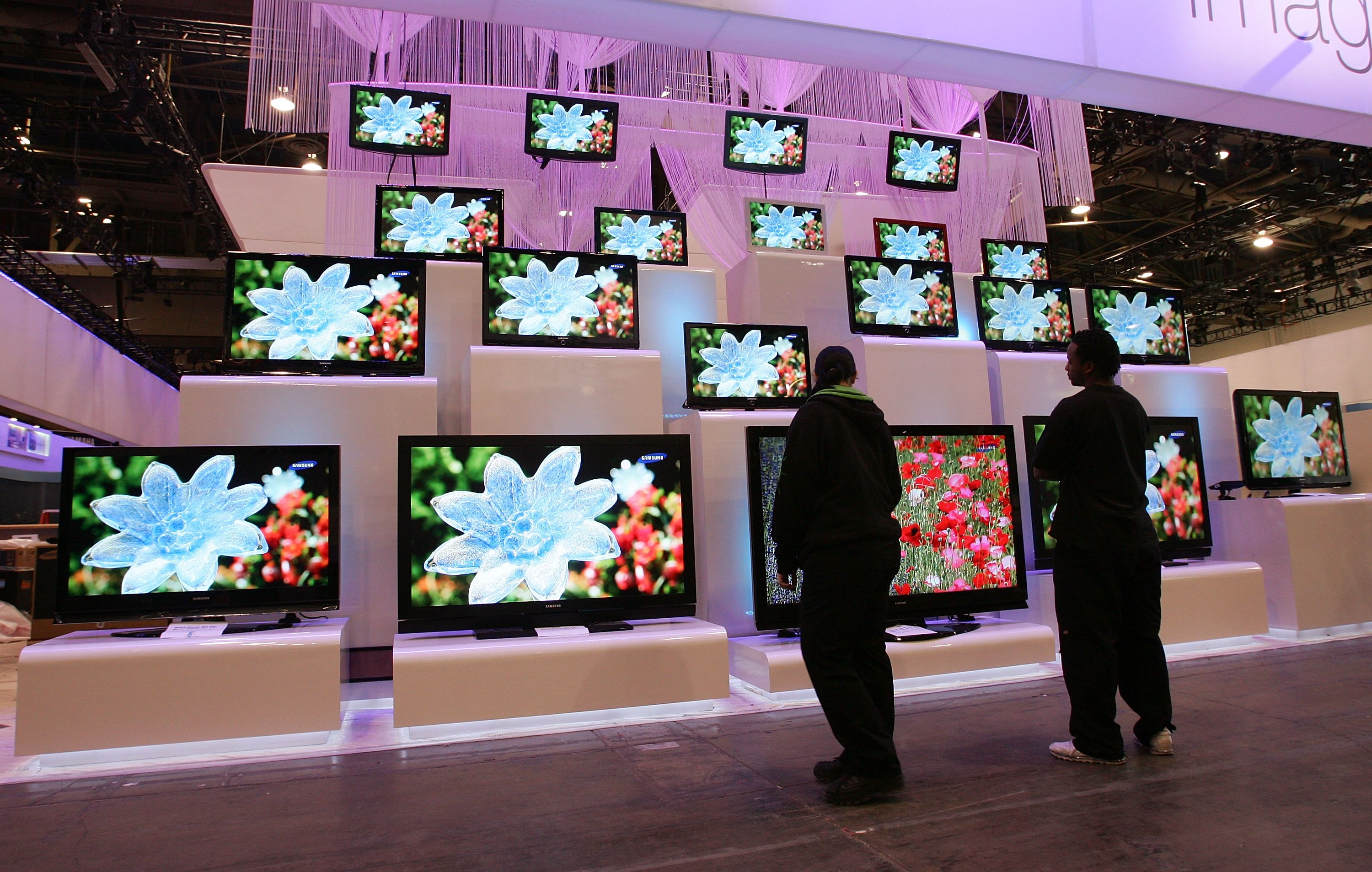 Workers look at a display of televisions by Samsung at the Las Vegas Convention Center as preparations continue for the opening of the 2007 International Consumer Electronics Show January 5, 2007 in Las Vegas, Nevada.