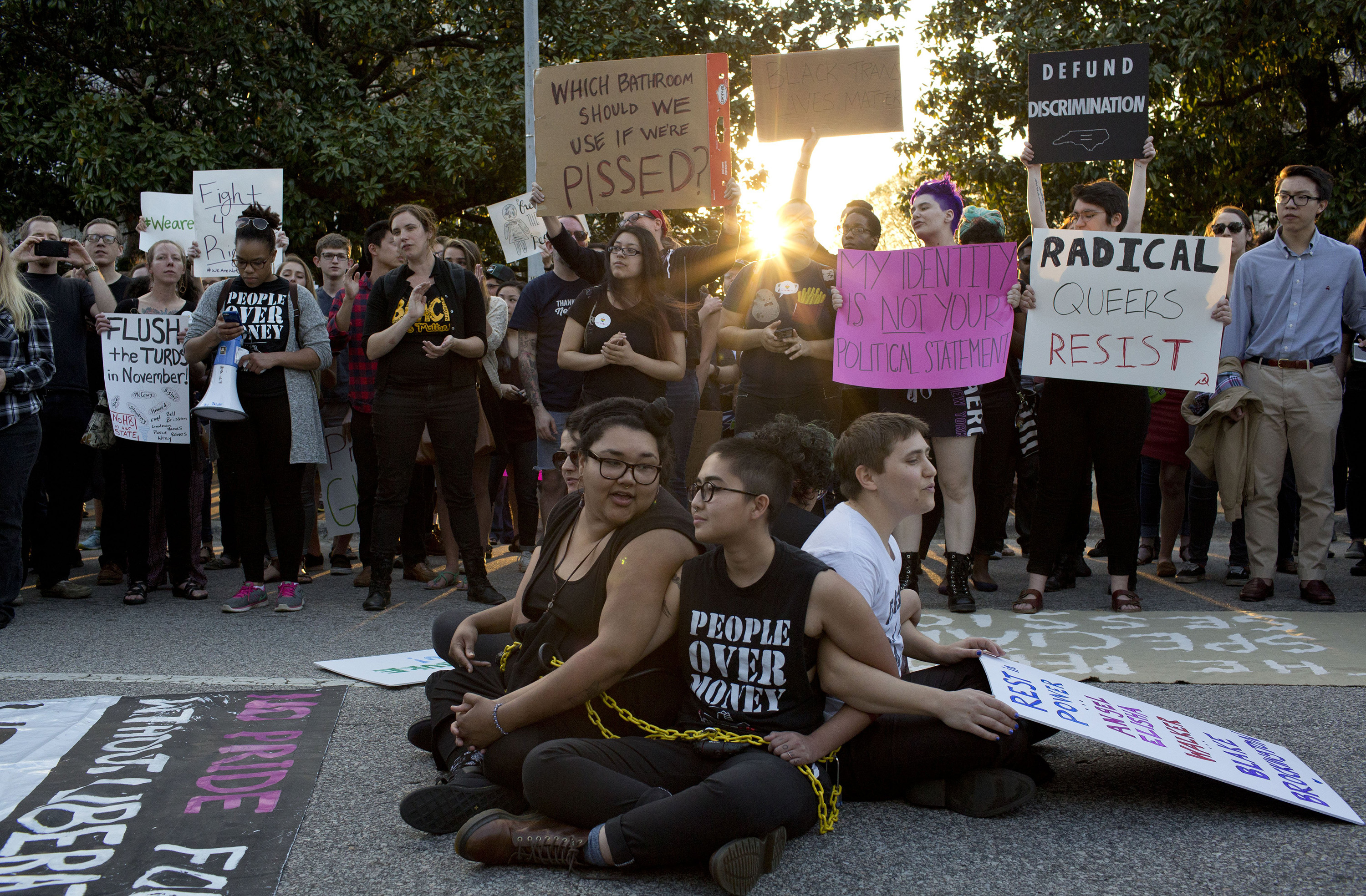 Front from left, demonstrators Jess Jude, Loan Tran and Noah Rubin-Blose, sit chained together in the middle of the street during a protest against House Bill 2 outside of the Governor's Mansion in Raleigh, N.C., on  March 24, 2016,.