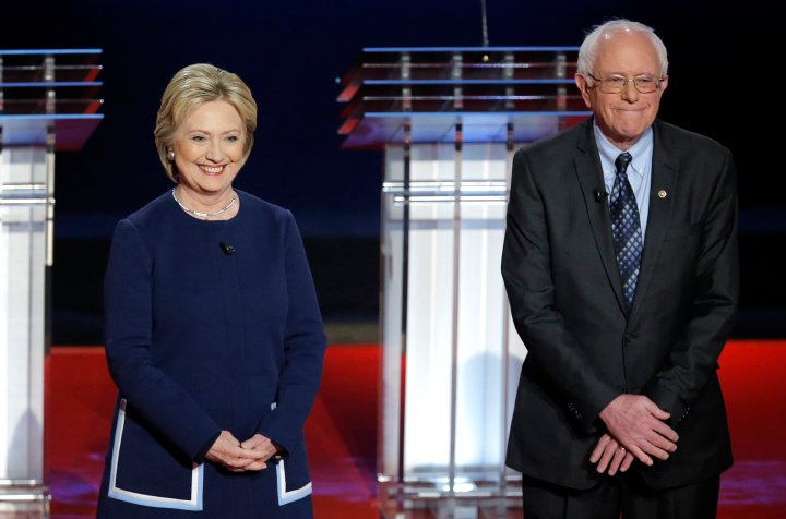 Hillary Clinton and Bernie Sanders pose together onstage at the start of the U.S. Democratic presidential candidates' debate in Flint, Michi. on March 6, 2016.