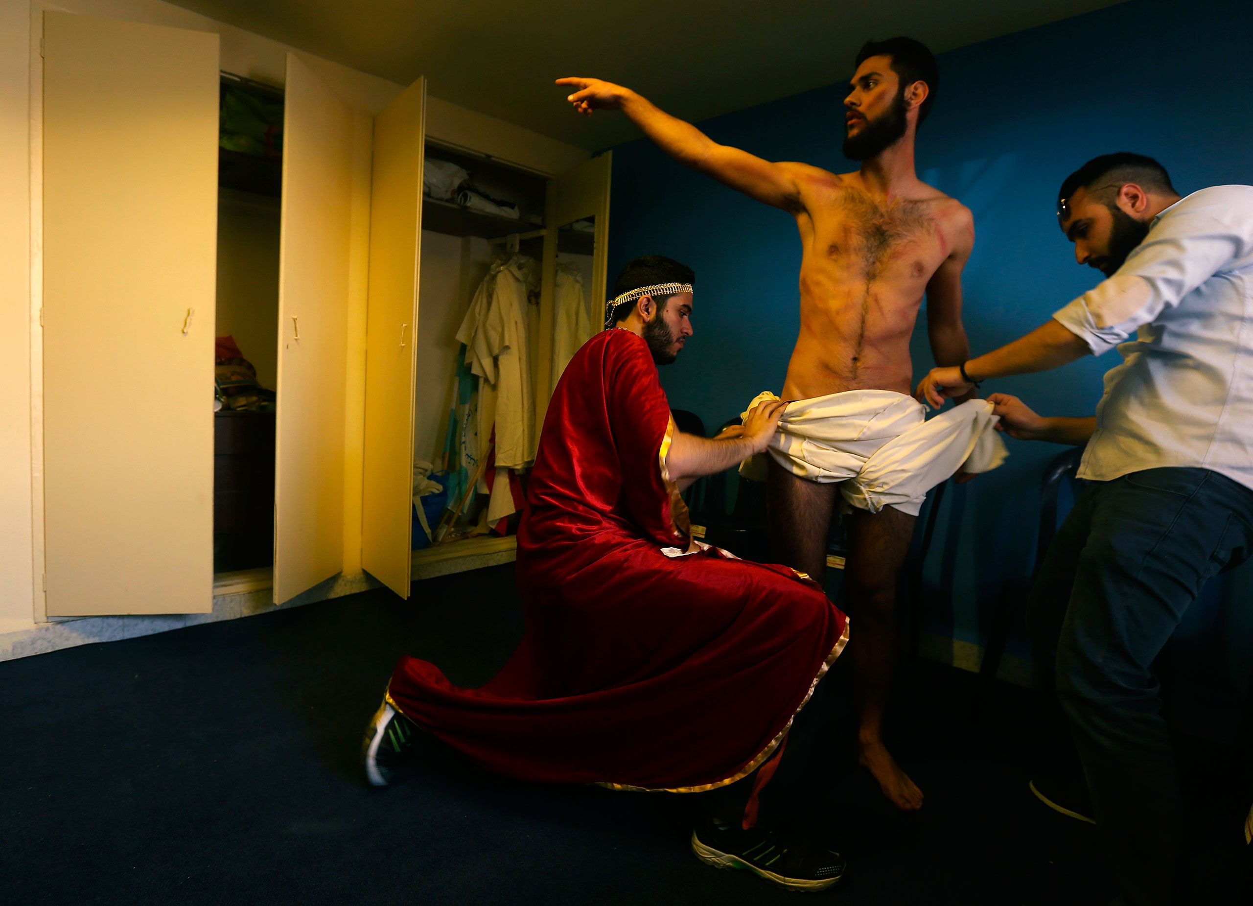Lebanese Christians prepare the character playing Jesus as they reenact the crucifixion of Christ during Holy Friday in the Christian village of Qraiye, east of Sidon, Lebanon, March 25, 2016.