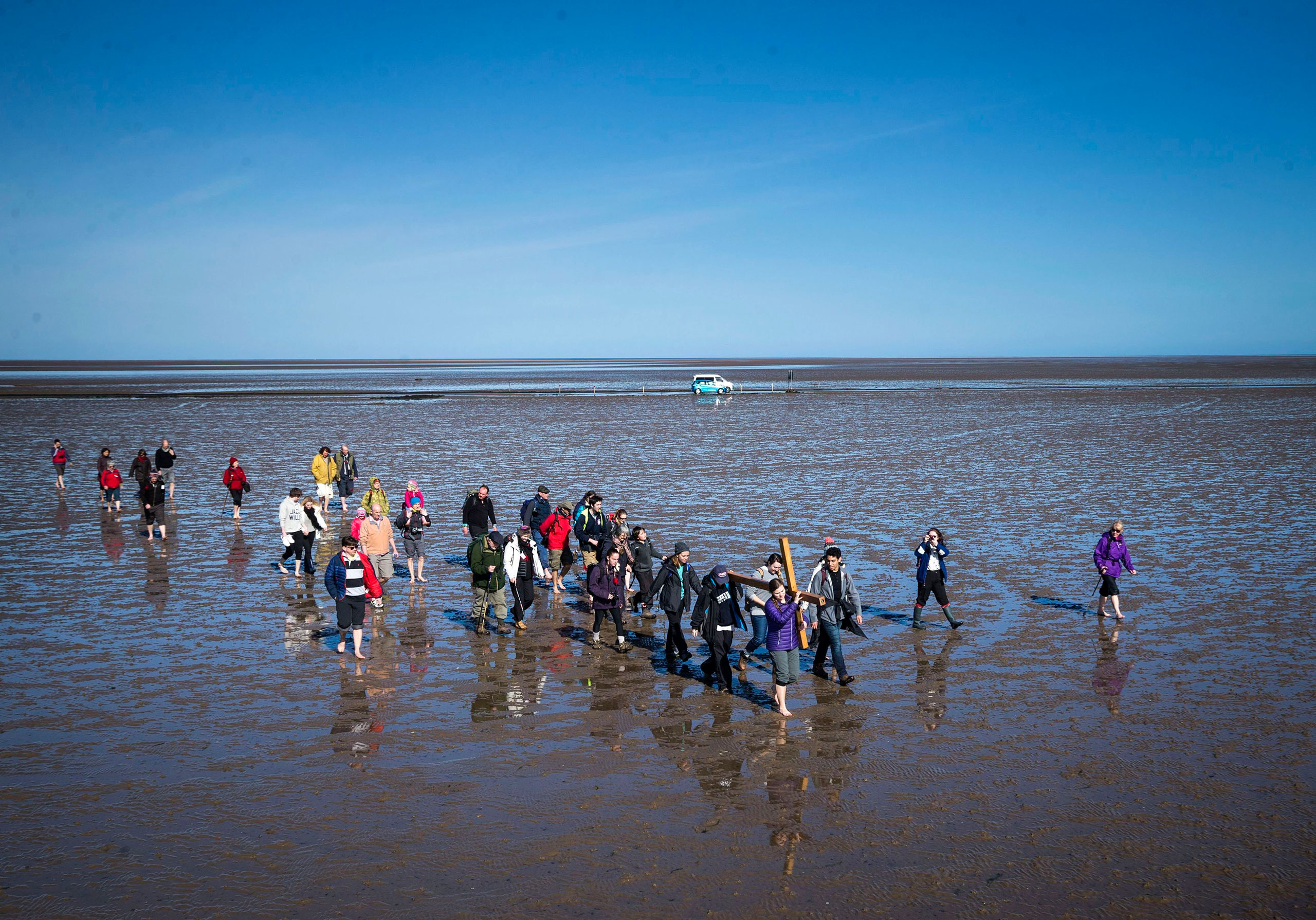 Pilgrims carry a cross on the final leg of the Northern Cross pilgrimage to Holy Island near Berwick-upon-Tweed in Northumberland, England, March 25, 2016.