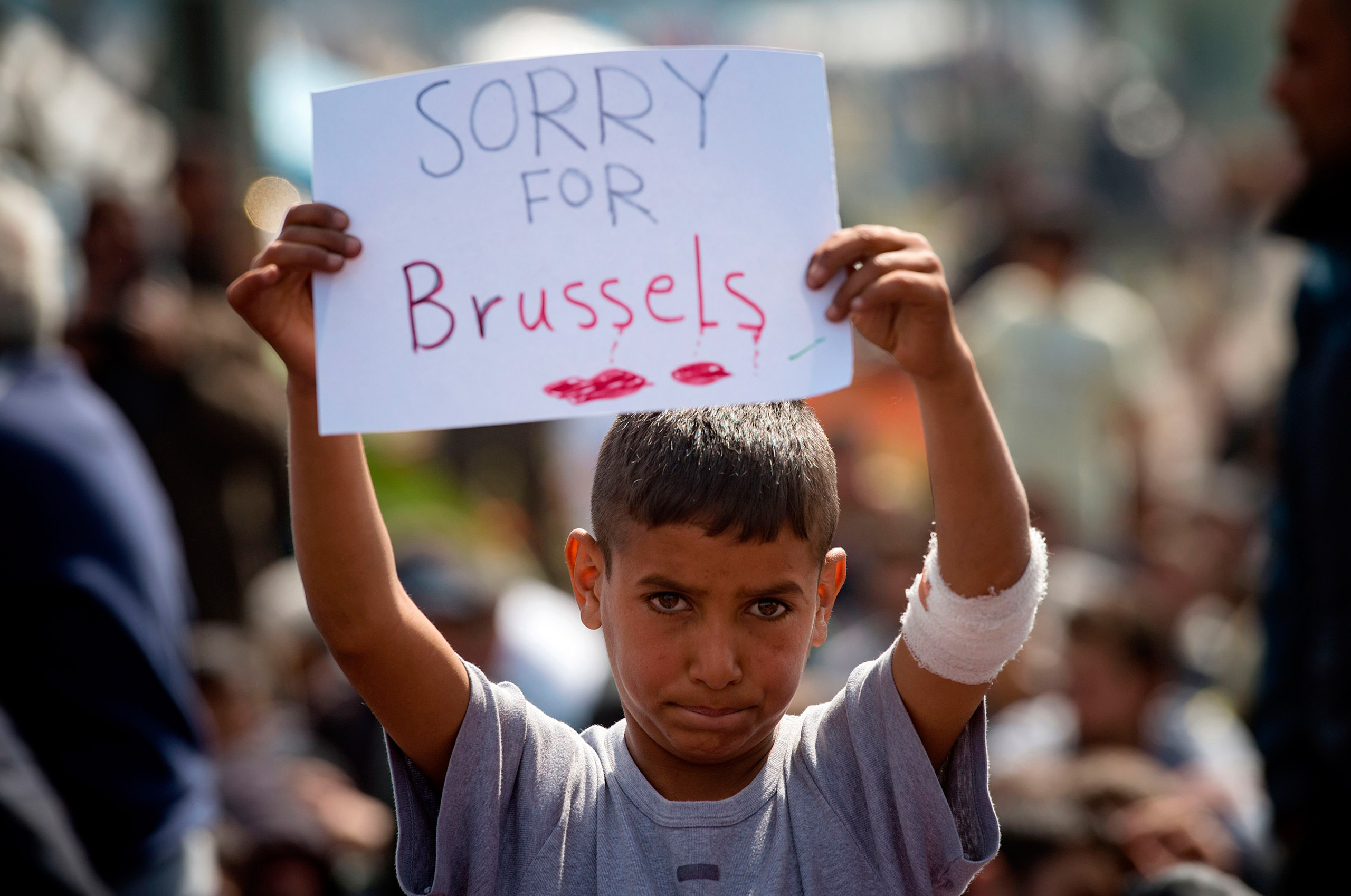 A boy holds a placard expressing sympathy for the victims of the terror attacks in Brussels during a protest at a makeshift camp at the Greek-Macedonian border, near the village of Idomeni, March 22, 2016.