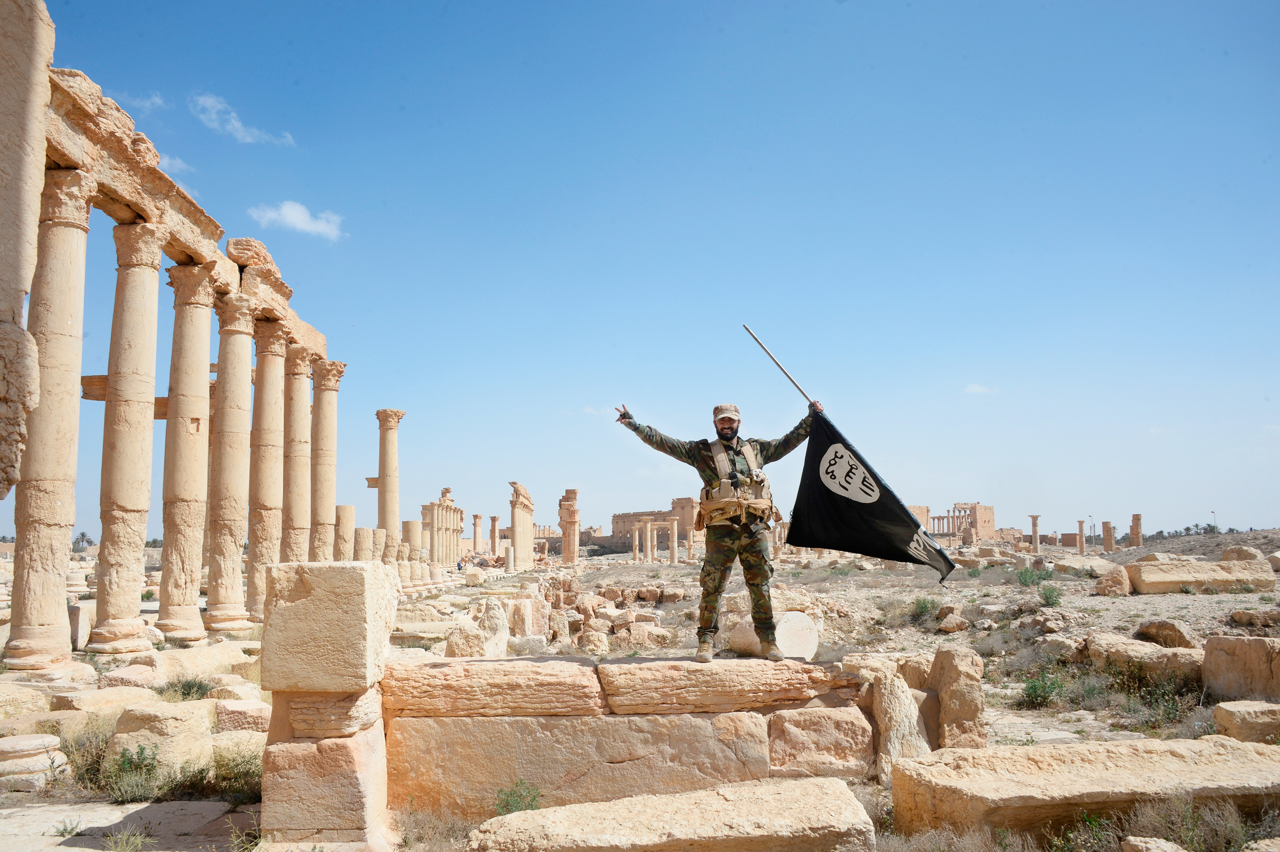 A Syrian army soldier holds an ISIS flag after government troops retake the city of Palmyra