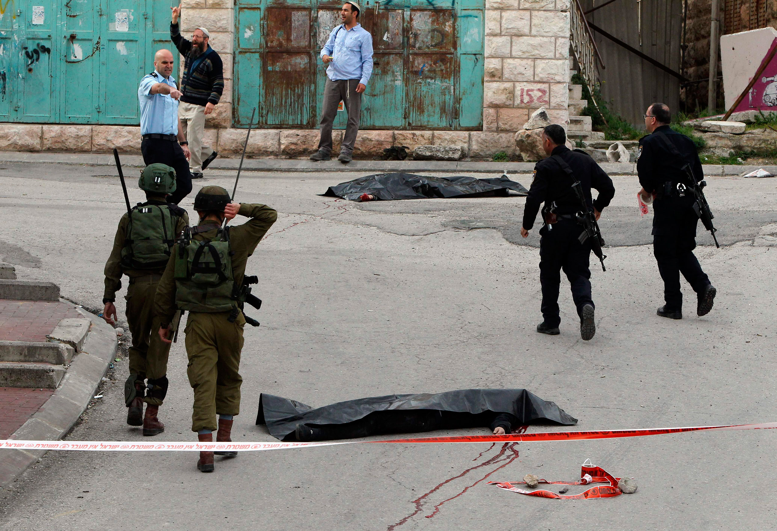 Israeli soldiers and police officers walk near the bodies of two Palestinians who were killed after wounding an Israeli soldier in a knife attack, before being shot dead by troops, in Hebron, West bank, March 24, 2016.