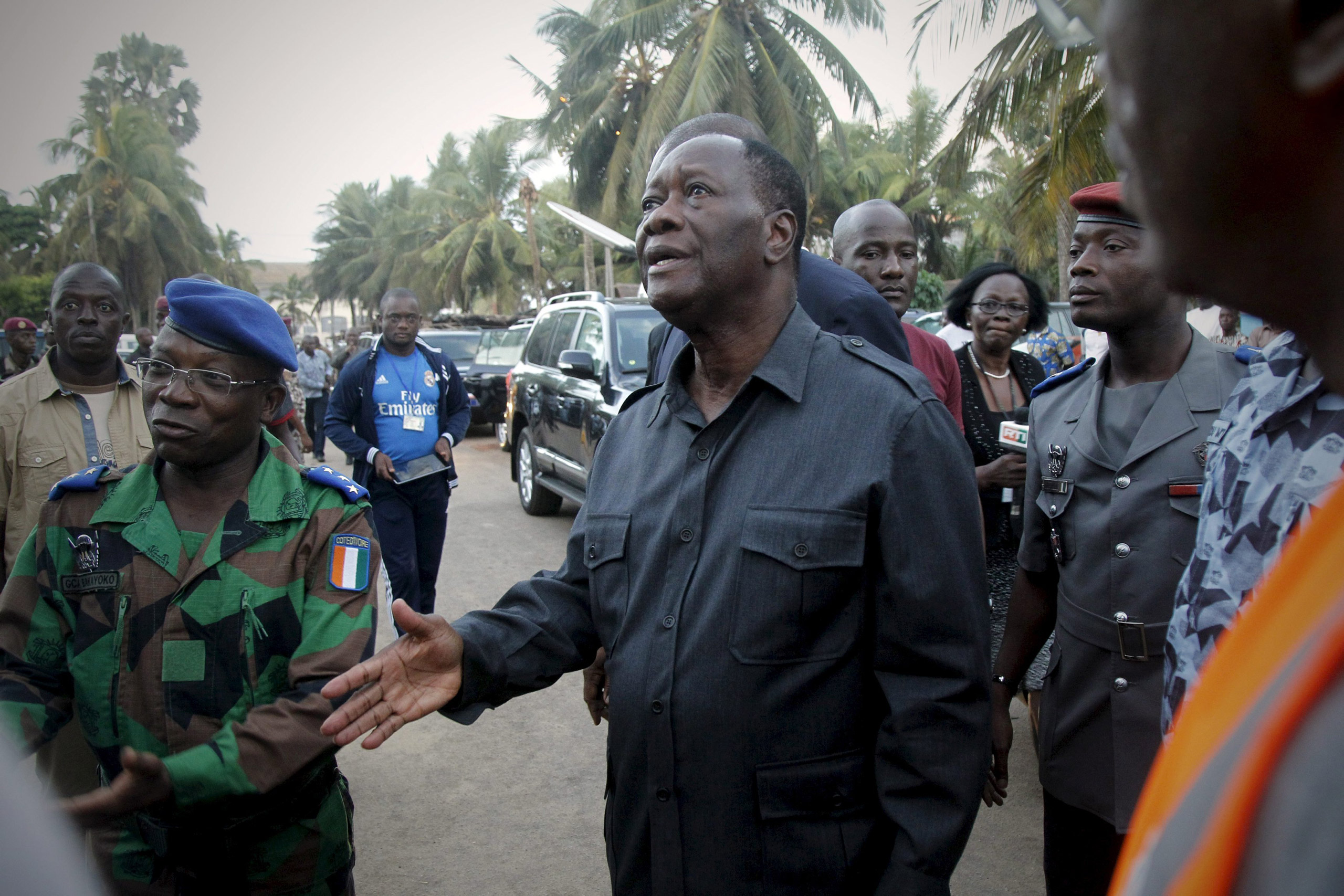 Ivory Coast's President Alassane Ouattara reacts next to Ivory Coast's army chief Soumaila Bakayoko as he arrives at the hotel Etoile du Sud after the attacks in Grand Bassam, Ivory Coast, on March 13, 2016.