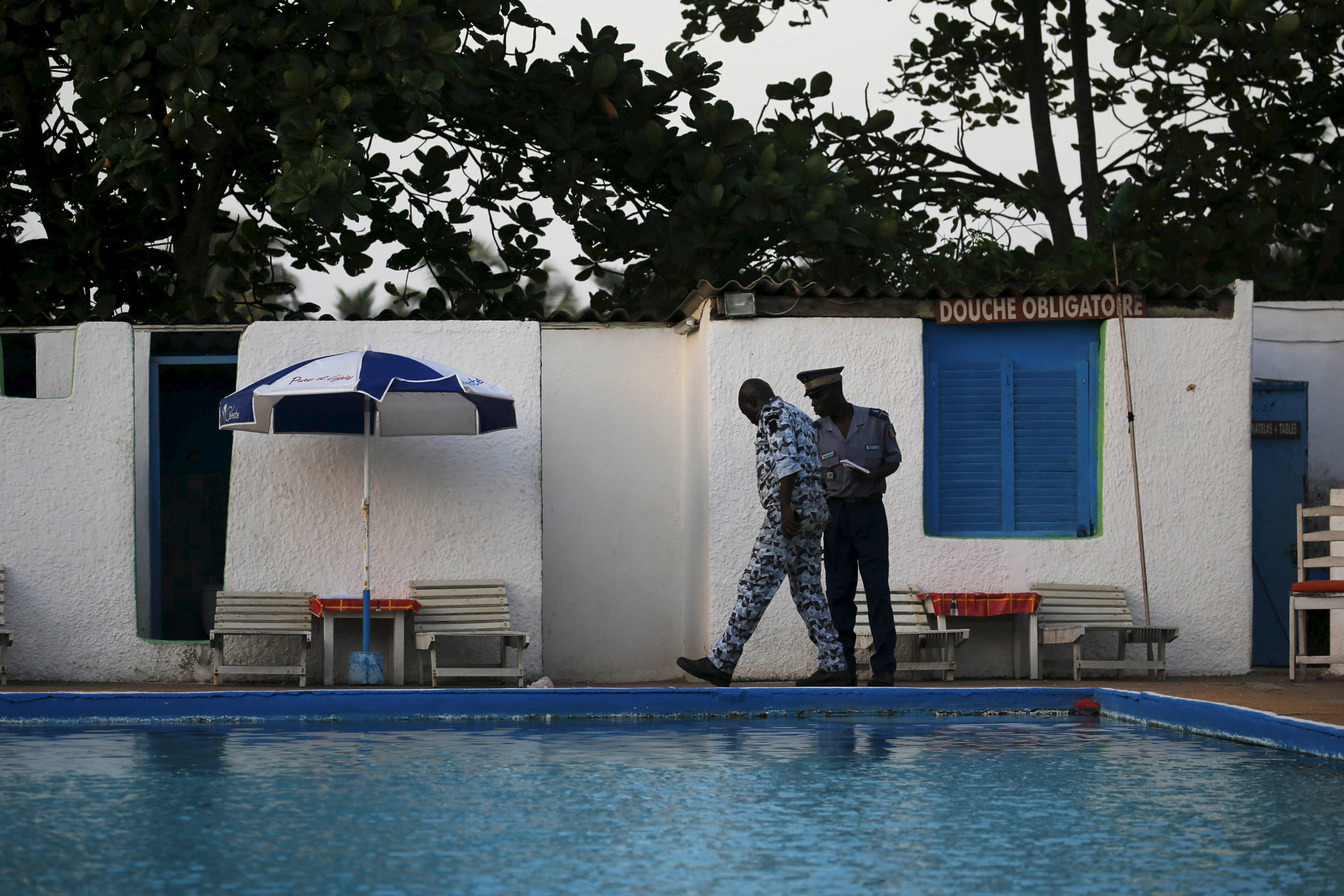 Security officers examine a hotel after an attack in Grand Bassam, Ivory Coast, on March 13, 2016.