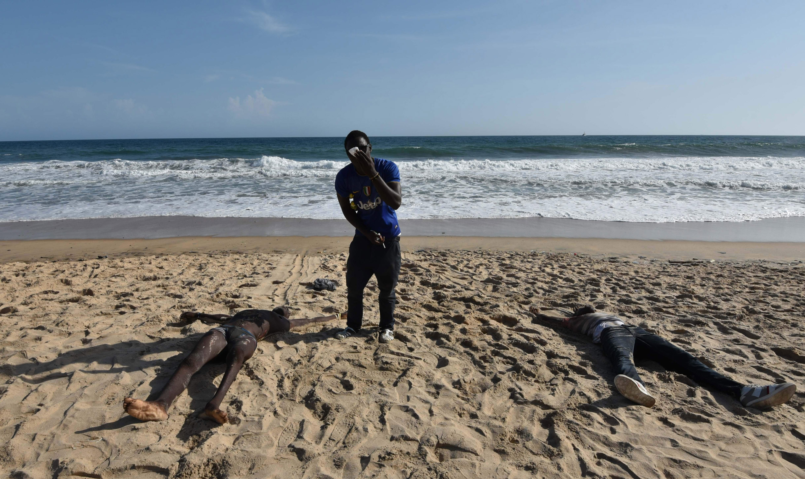Bodies are seen on a beach after heavily armed gunmen opened fire at a beach resort in Grand-Bassam, Ivory Coast, on March 13, 2016.