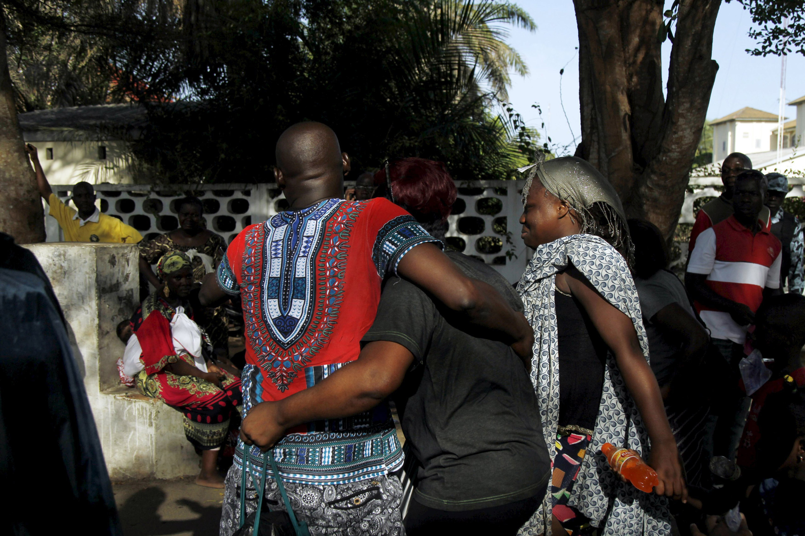 People comfort each other after the attacks in Grand-Bassam, Ivory Coast, on March 13, 2016.