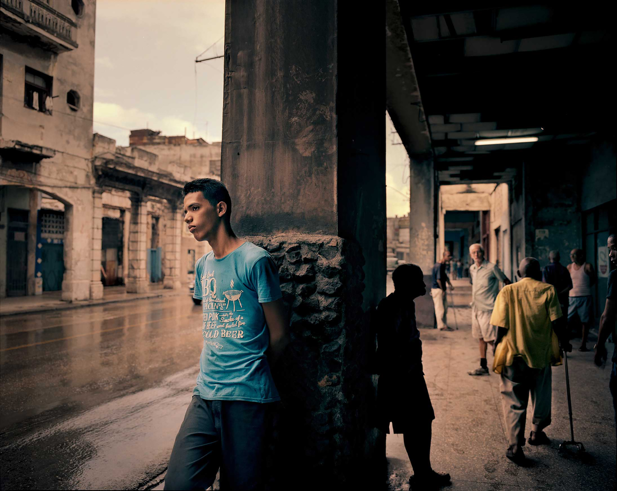 People find shelter from the rain, under old porches, in Havana.