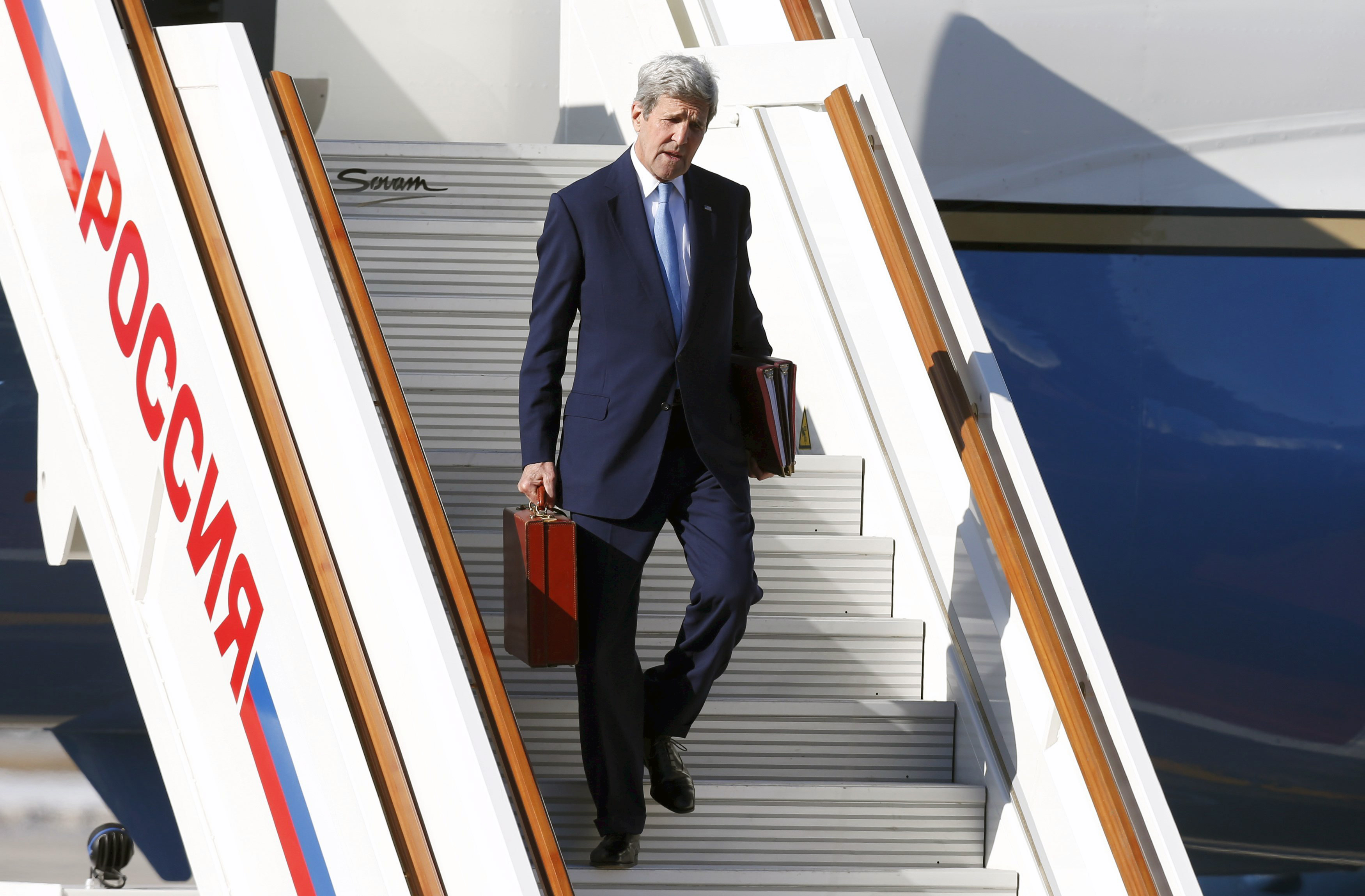 U.S. Secretary of State John Kerry carries his briefcase as he arrives at Moscow's Vnukovo airport in Russia, on March 23, 2016.