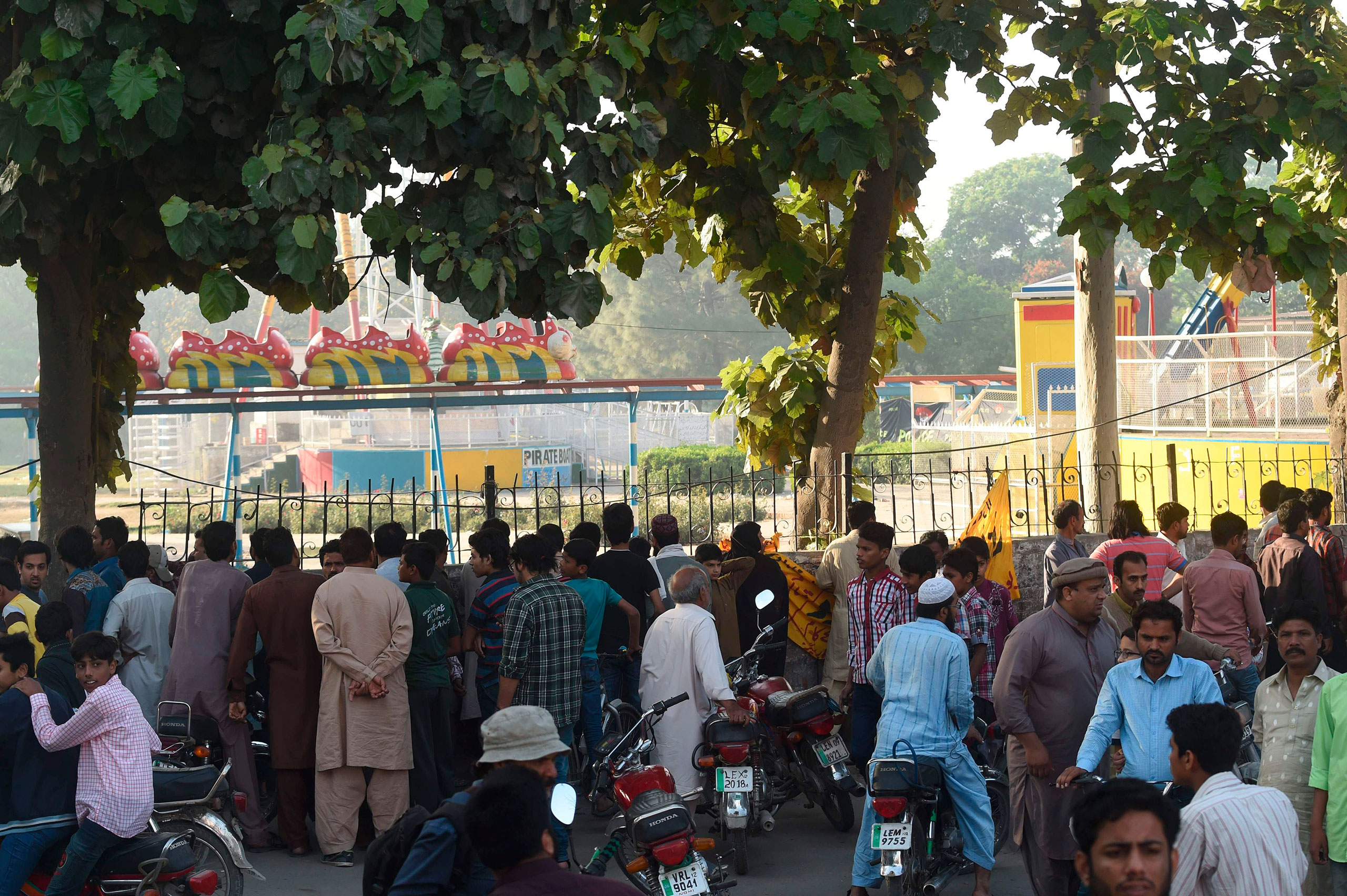 Local residents gather outside the cordoned-off site of the bombing at the park in Lahore, Pakistan, on March 28, 2016