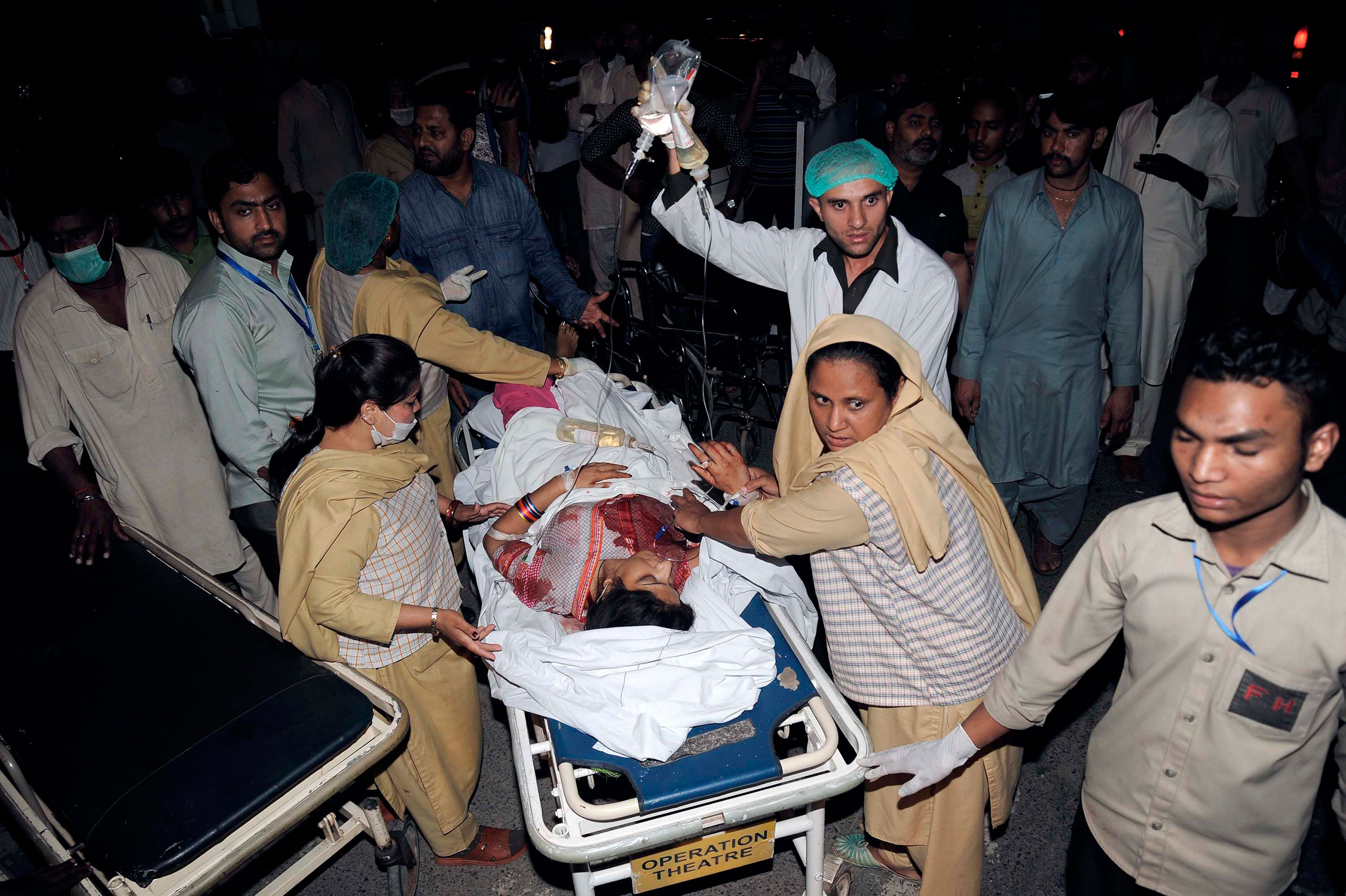 Relatives and emergency workers carry an injured woman to the hospital after at least 70 people were killed in an Easter Sunday bombing at a park in Lahore, Pakistan, on March 27, 2016