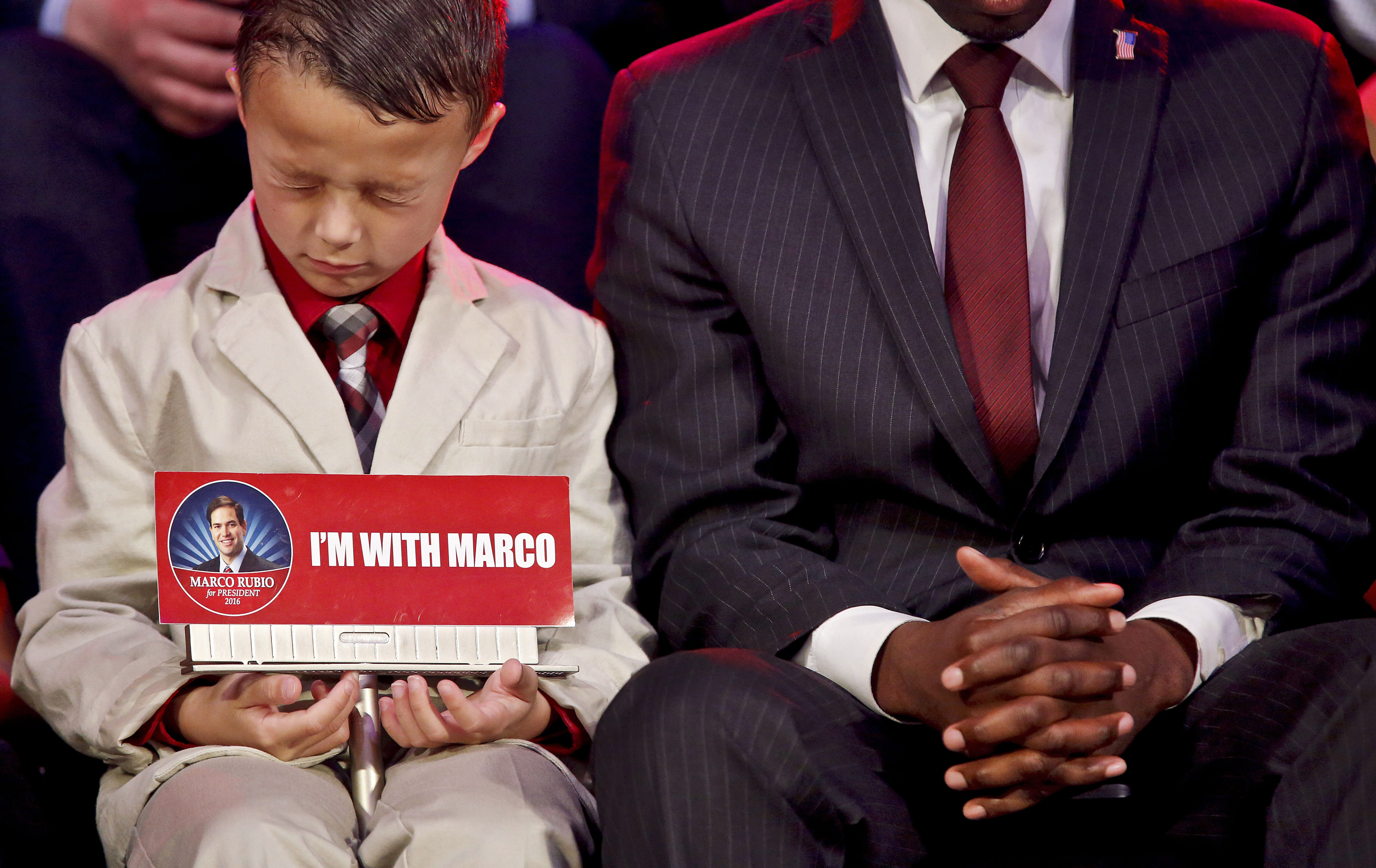 Six-year-old Aiden Thurman, of Hugo, Okla. prays during a campaign stop by Republican presidential candidate Marco Rubio on Feb. 26, 2016, in Oklahoma City.