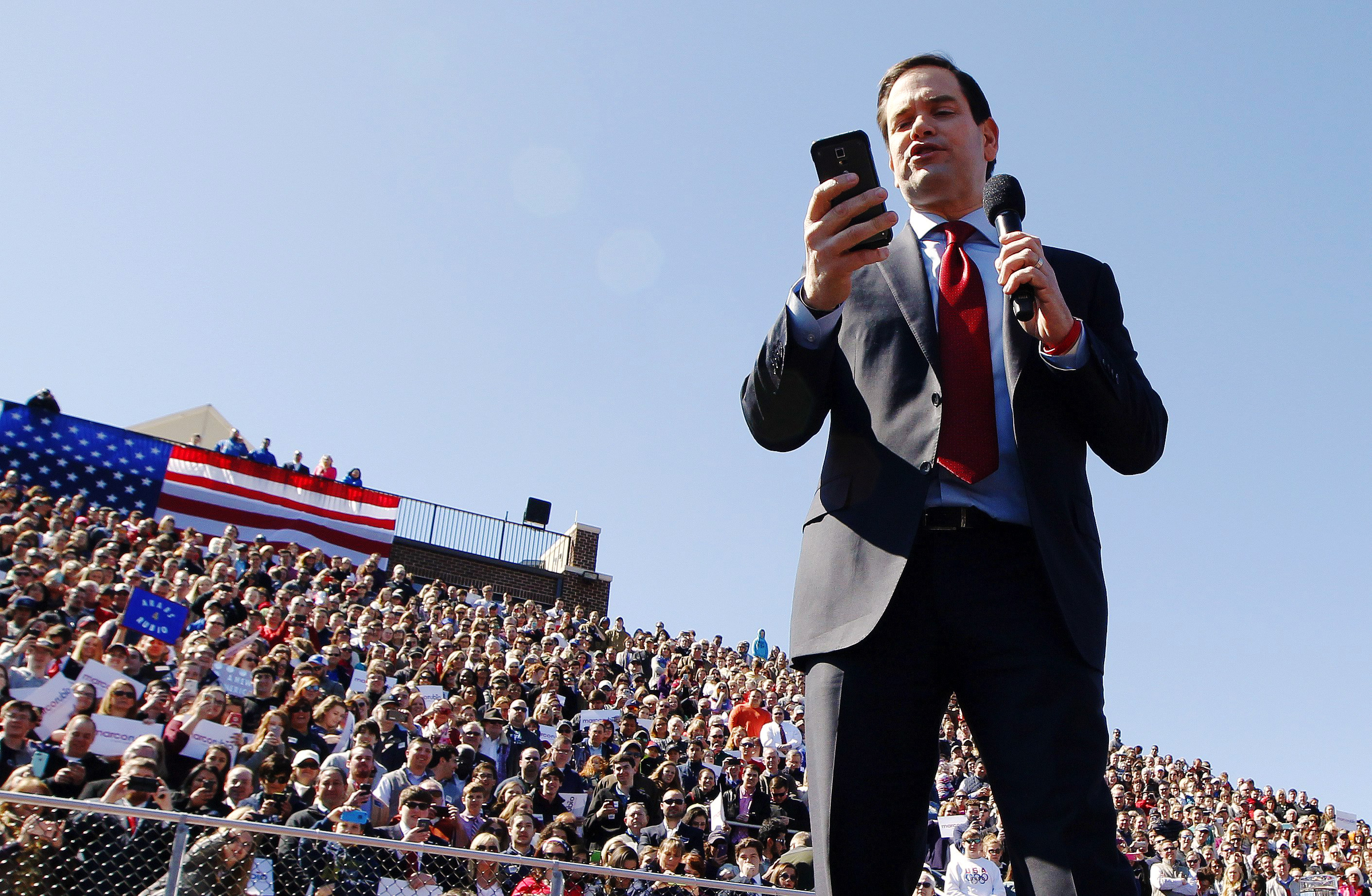 Republican presidential candidate, Florida Sen. Marco Rubio reads tweets from Donald Trump during a rally at Mount Paran Christian school in Kennesaw, Ga. on Feb. 27.