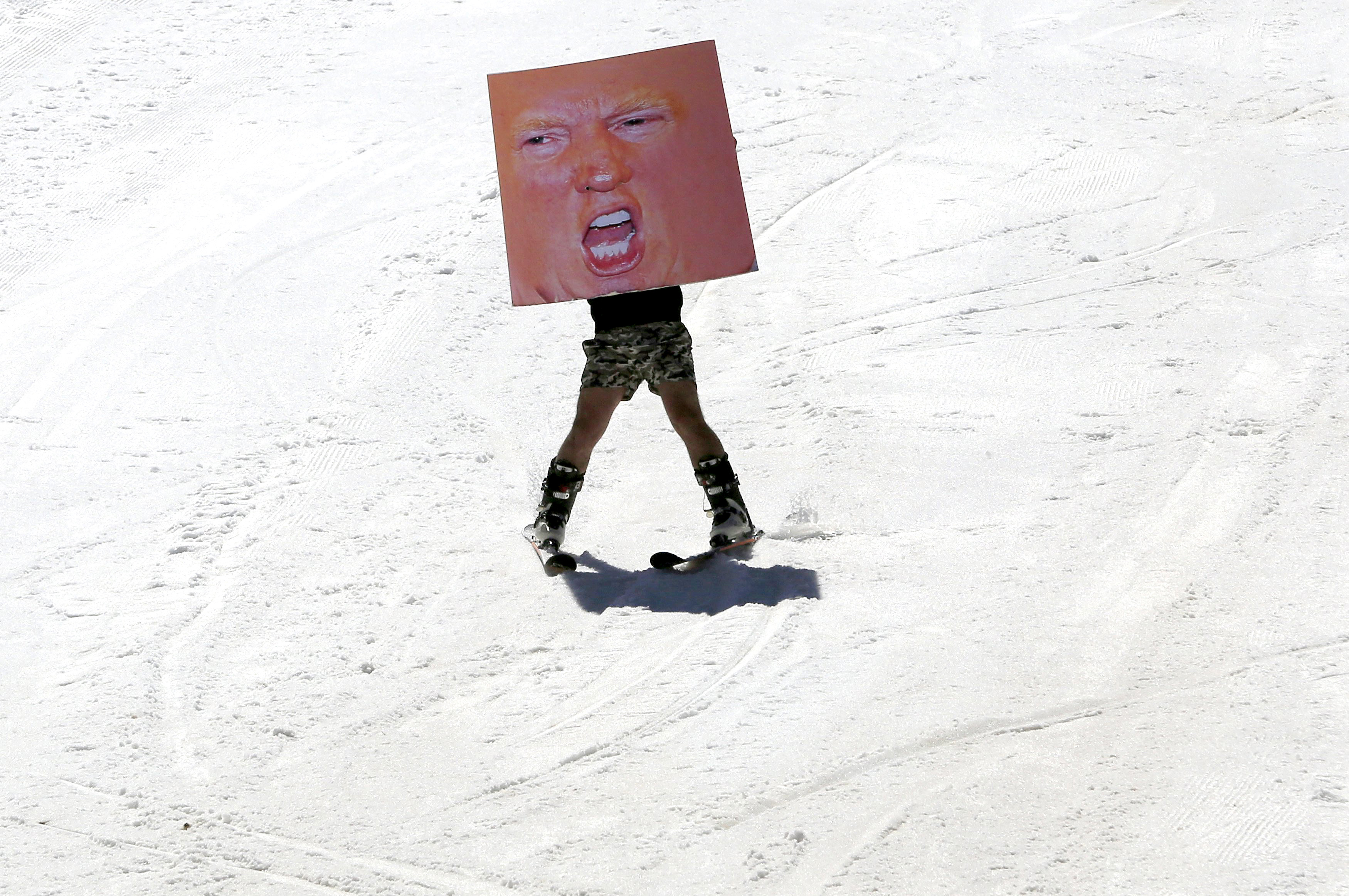 A man holds a poster depicting Donald Trump while participating in Red Bull Jump & Freeze Lebanon at a ski resort in mount Lebanon on Feb. 28.
