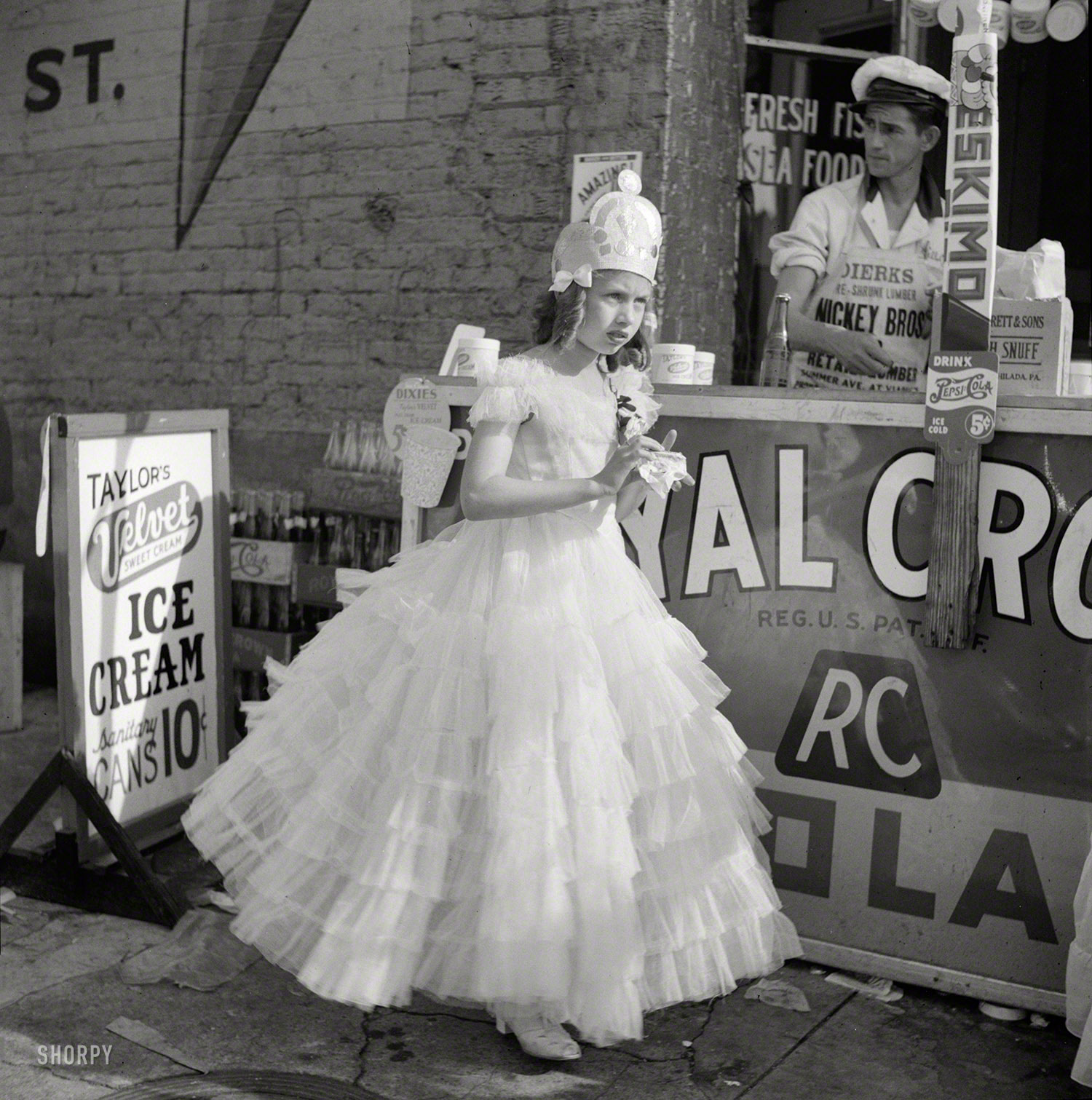 Marion Post (1910–1990)Marion Post Wolcott, was   an American photographer who worked for the Farm Security Administration during the Great Depression documenting poverty and deprivation.                               Post's photographs for the FSA often explore the political aspects poverty as well as finding the humour in the situations she encountered. Cotton Queen: May 1940.  Cotton carnival. Memphis, Tennessee.  Waiting for her Royal Crown