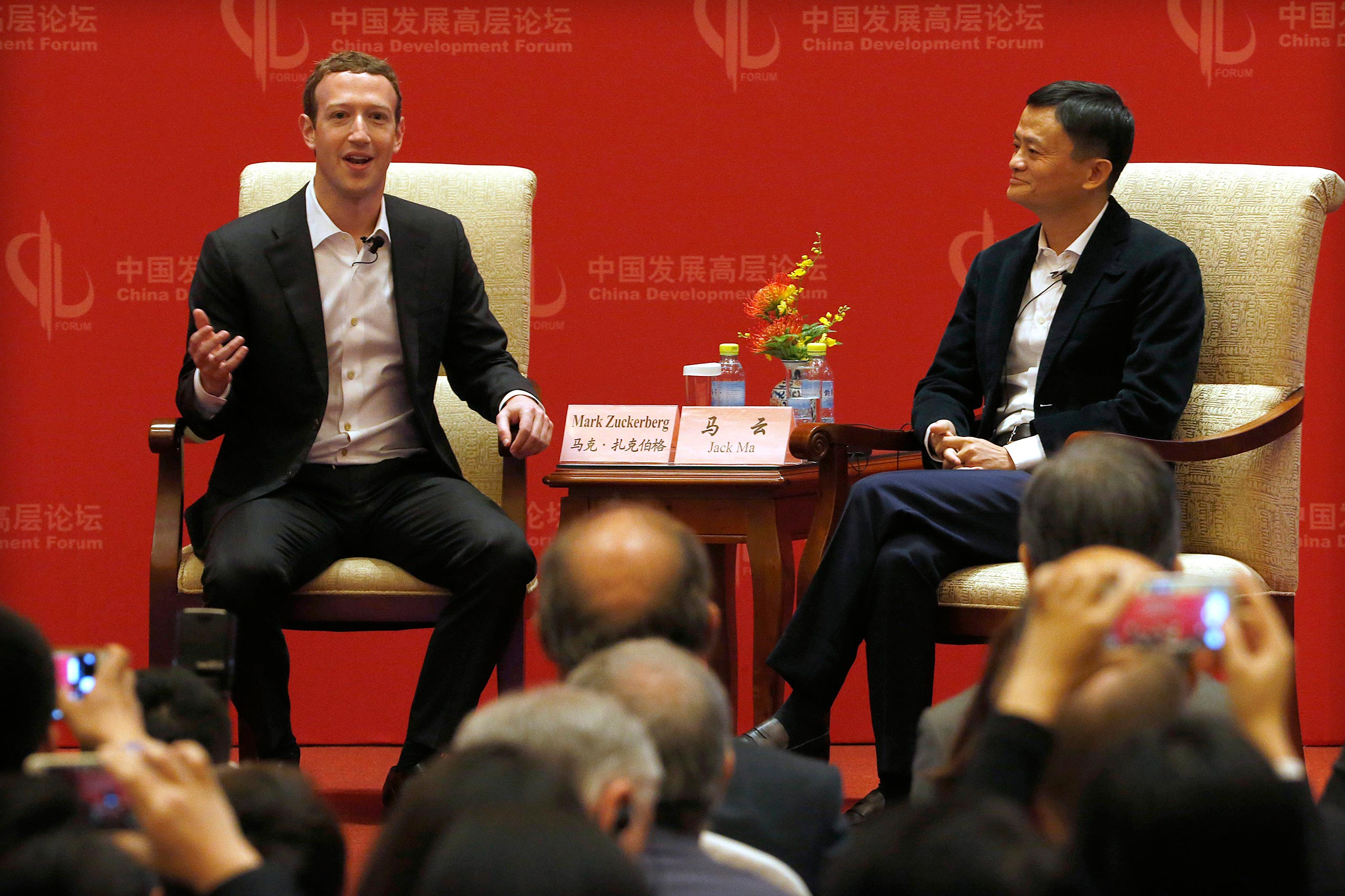 Facebook CEO Mark Zuckerberg speaks as Jack Ma, executive chairman of the Alibaba Group, listens during a panel discussion held as part of the China Development Forum at the Diaoyutai State Guesthouse in Beijing on March 19, 2016