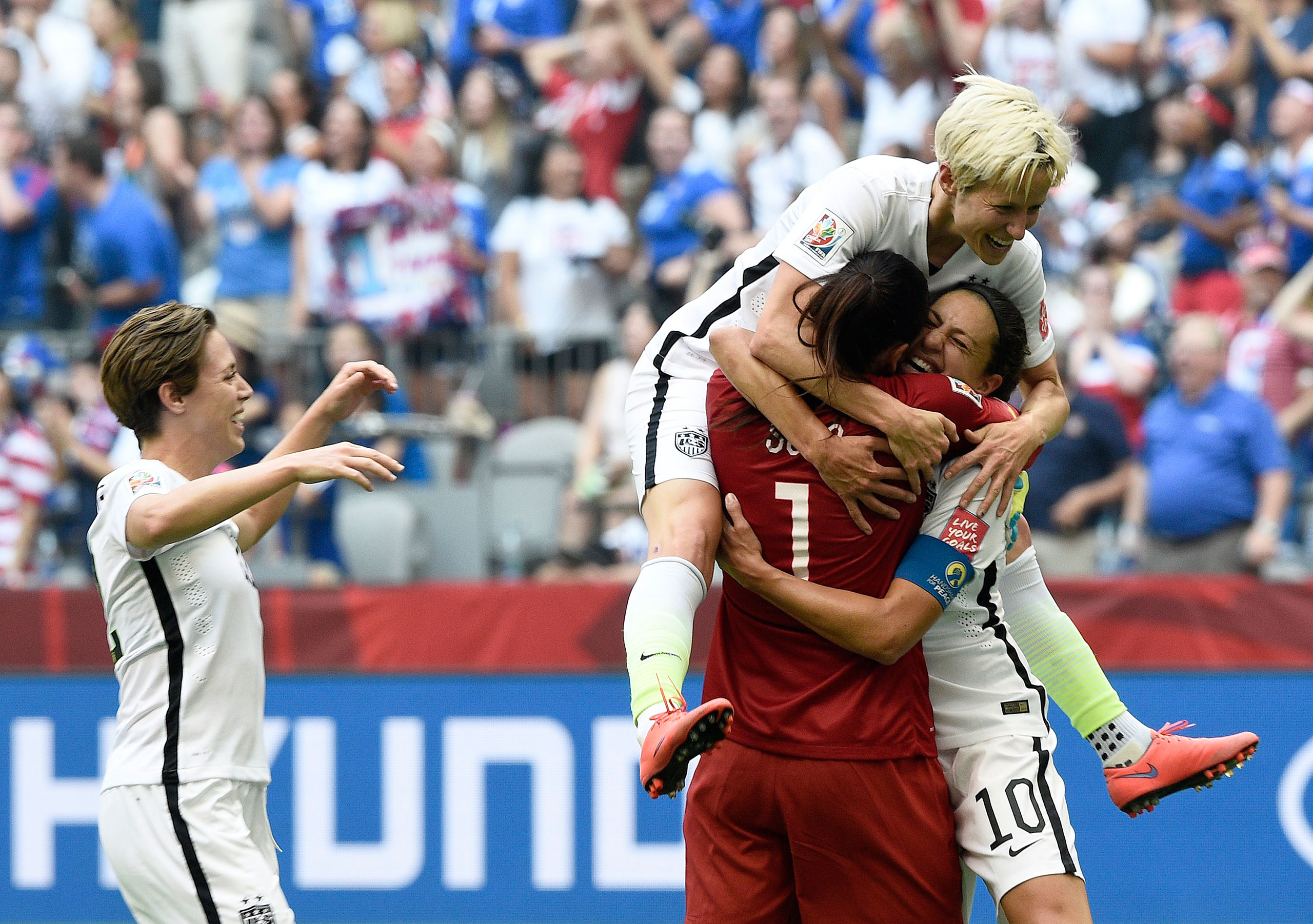 Carli Lloyd (10) is congratulated by goalkeeper Hope Solo (1) and midfielder Megan Rapinoe (top) after scoring a goal during the final match between USA and Japan during the 2015 FIFA Women's World Cup at the BC Place Stadium in Vancouver, Canada, July 5, 2015.
