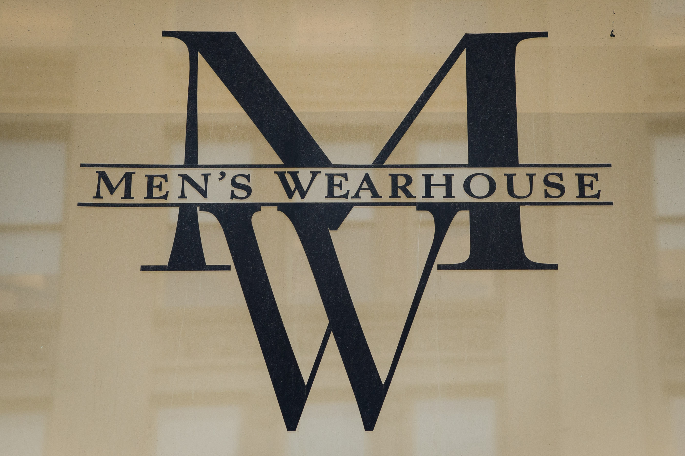 The Men's Wearhouse Inc. logo is displayed outside of a store on 6th Avenue in New York, U.S., on Monday, Dec. 2, 2013.