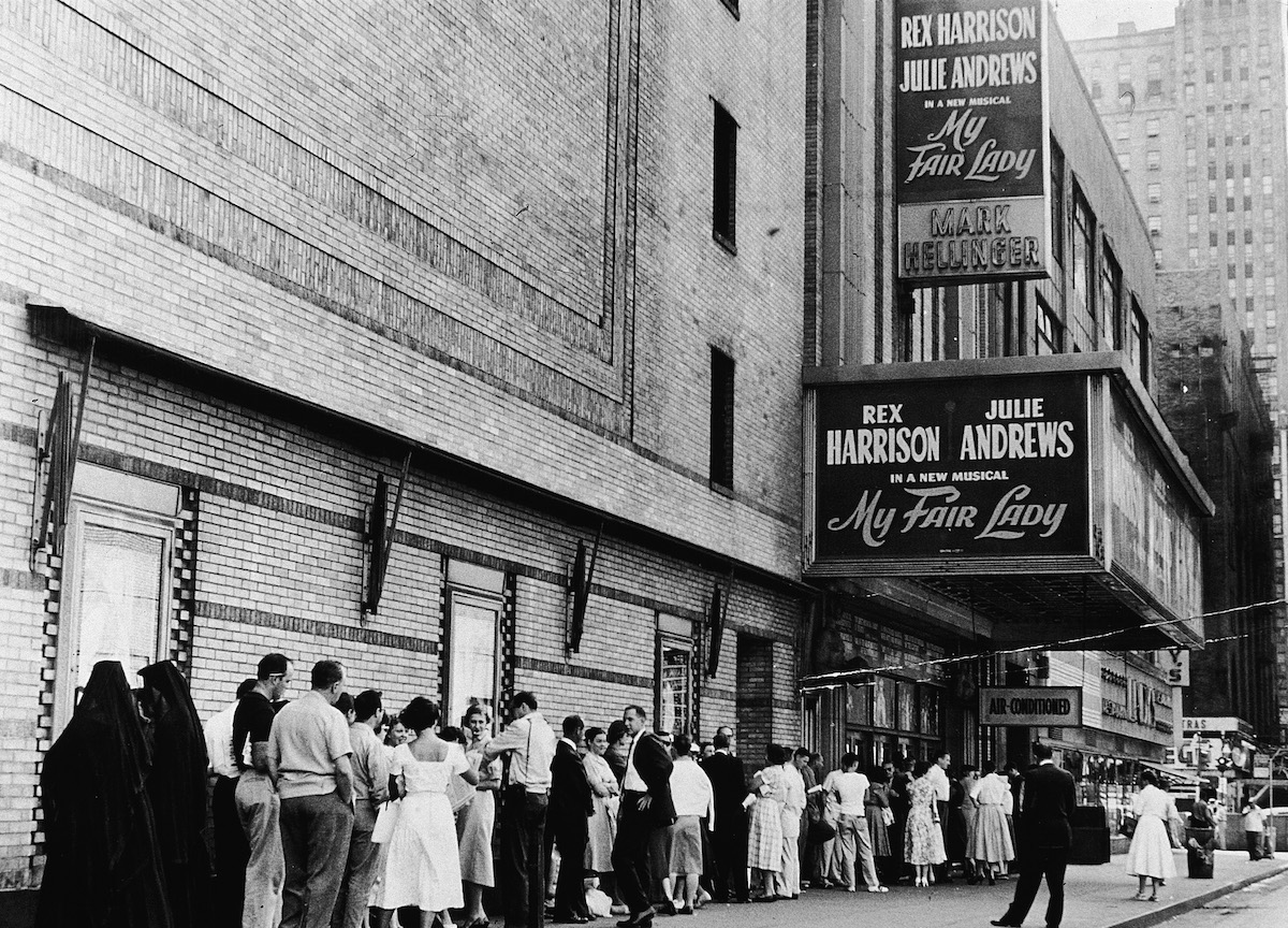 Crowds wait in line at 9:00 AM to purchase tickets for the stage musical, 'My Fair Lady,' starring Rex Harrison and Julie Andrews, at the Mark Hellinger Theatre, New York City, July 10, 1957.