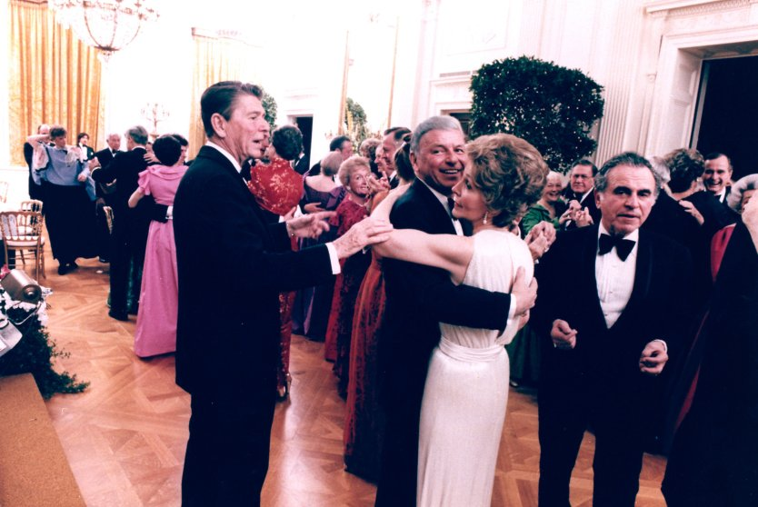 Ronald Reagan cuts in on singer Frank Sinatra, dancing with former first lady Nancy Reagan during a party in the East Room of the White House on Feb. 6, 1981.