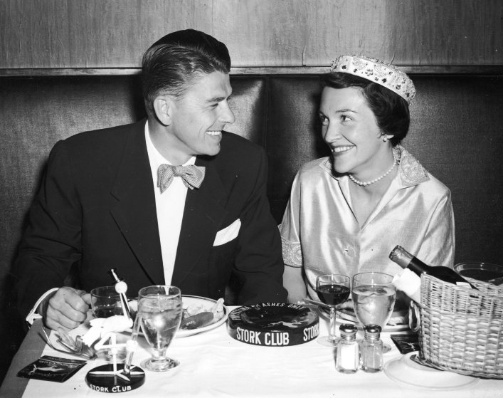 Ronald Reagan and his wife Nancy Reagan smile during their honeymoon dinner at the Stork Club in New York in 1952.