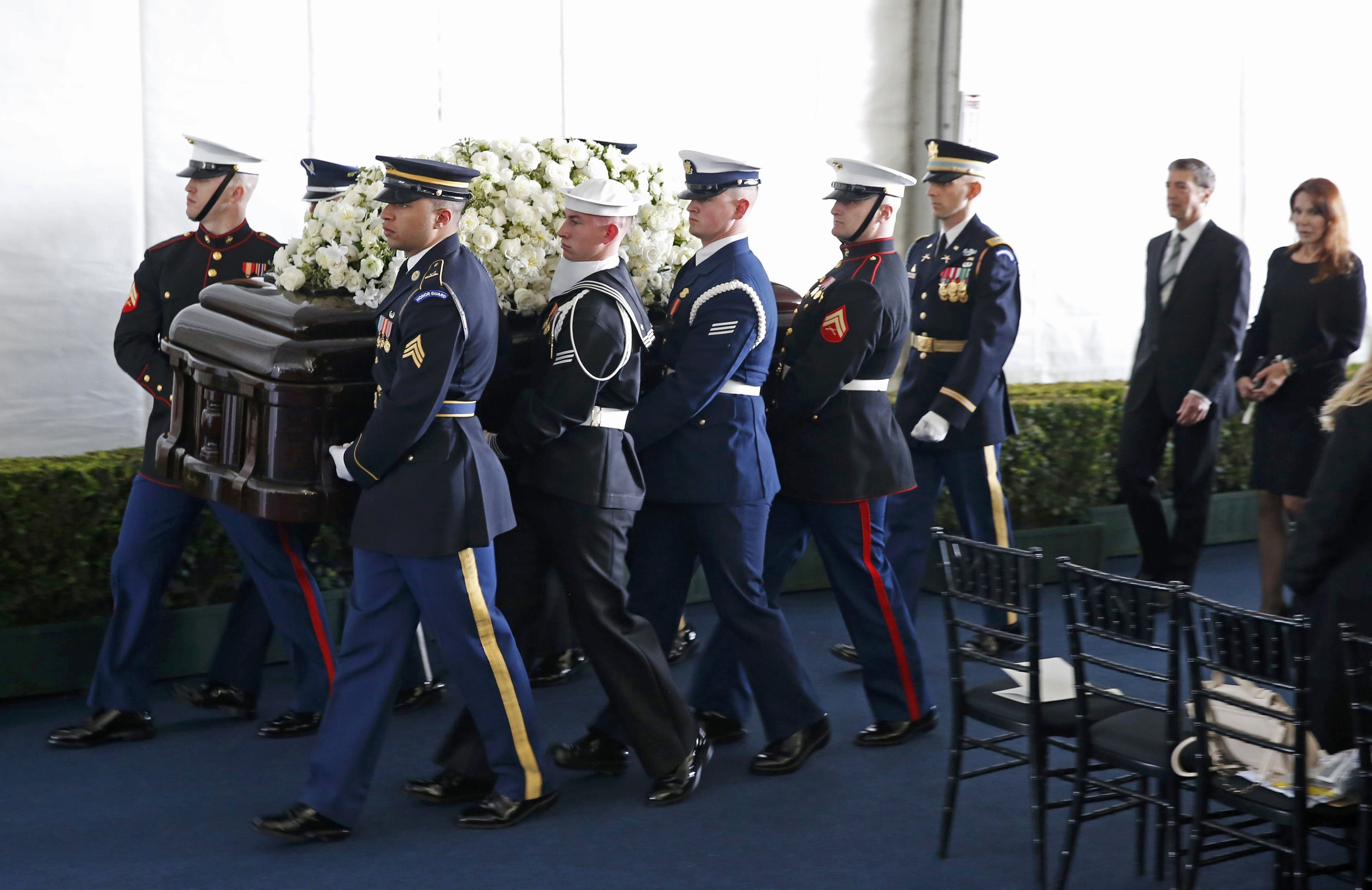 A military honor guard carries the casket and is followed by Nancy Reagan's son Ronald Prescott Reagan, and daughter Patti Davis after the funeral service, March 11, 2016.