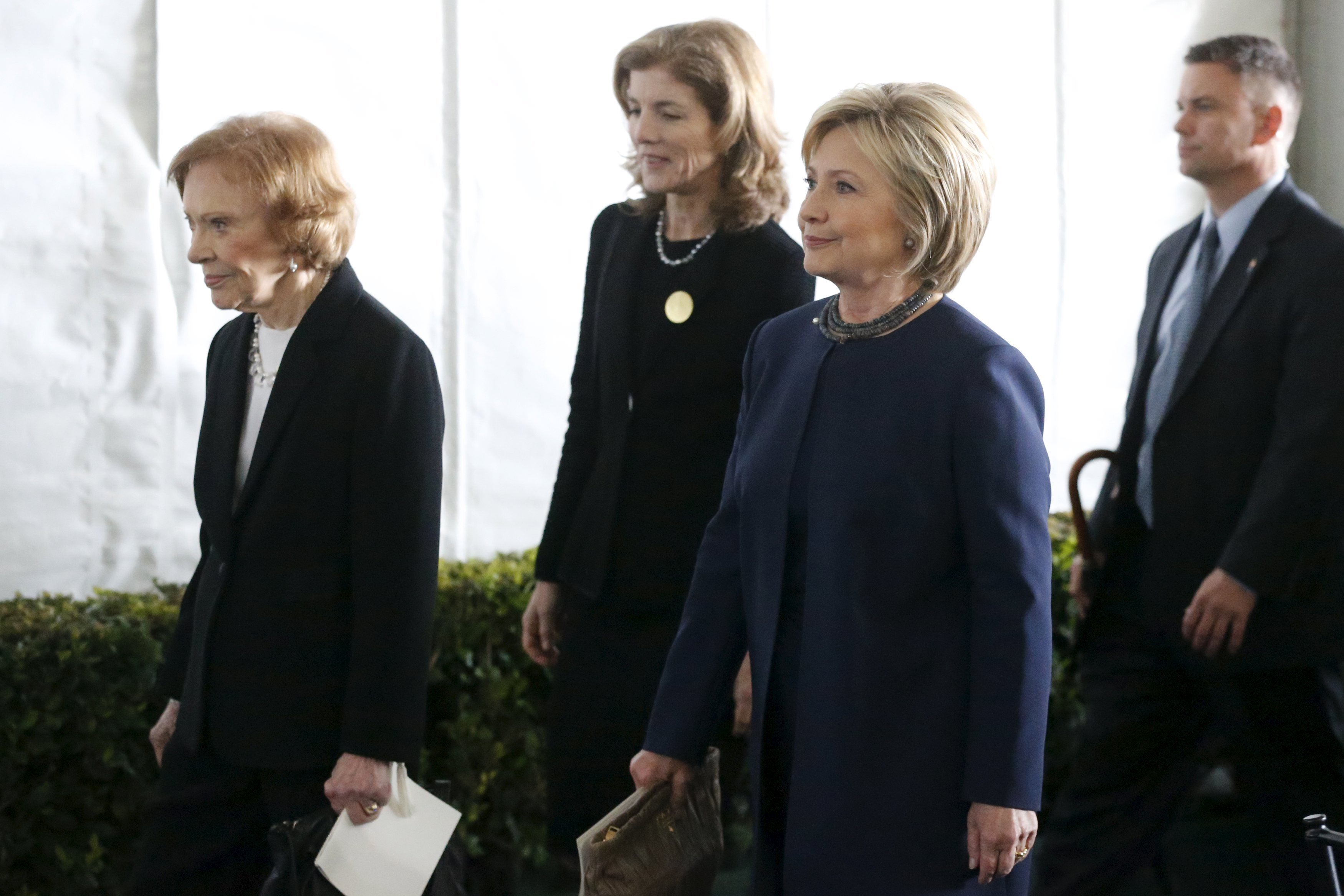 From left, Former first lady Rosalynn Carter, Caroline Kennedy, and Hillary Clinton walk to the grave site after the funeral at the Ronald Reagan Presidential Library, March 11, 2016.