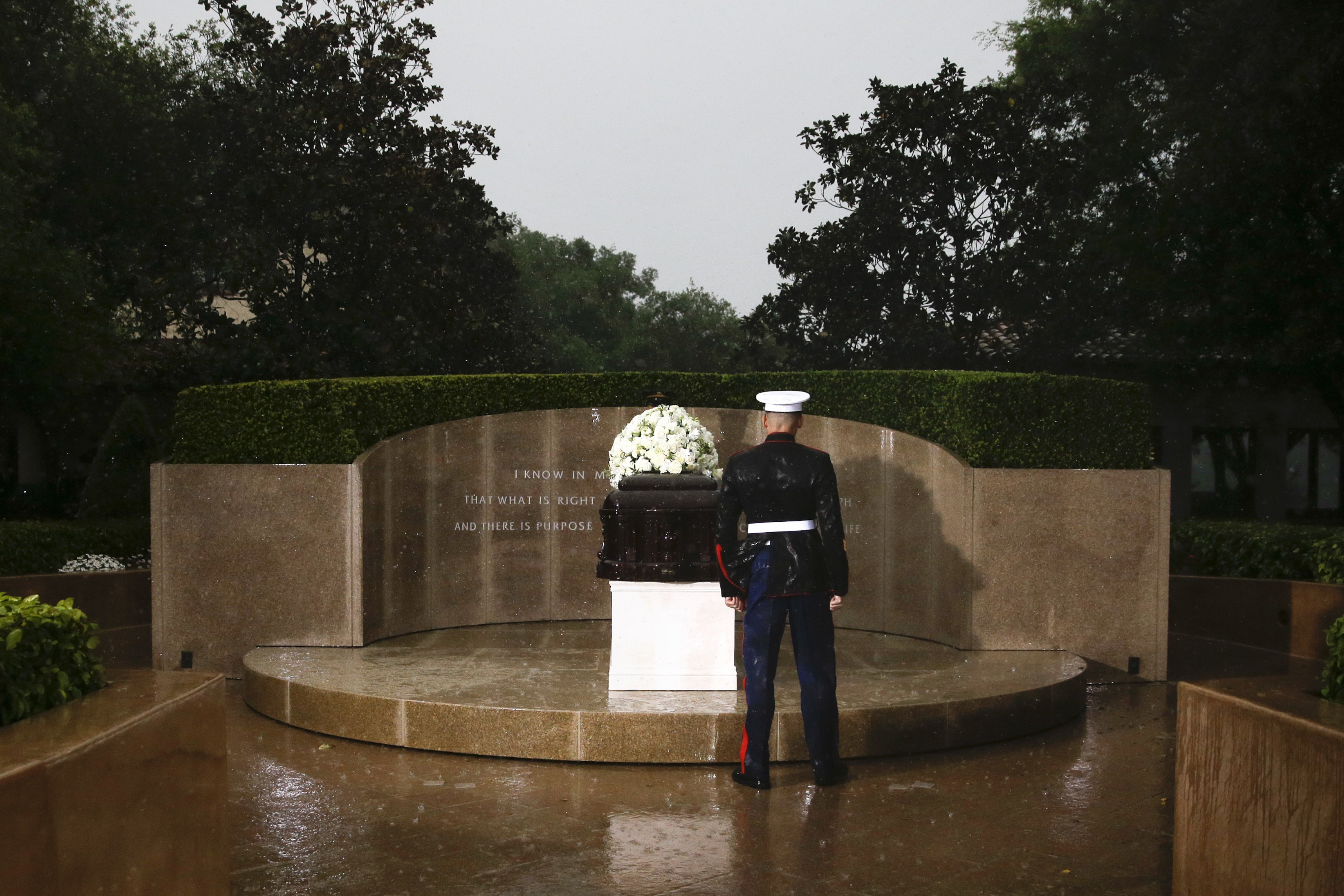 A Marine pays his respects in the rain while standing in front of the casket carrying former First Lady Nancy Reagan at the Ronald Reagan Presidential Library, March 11, 2016.