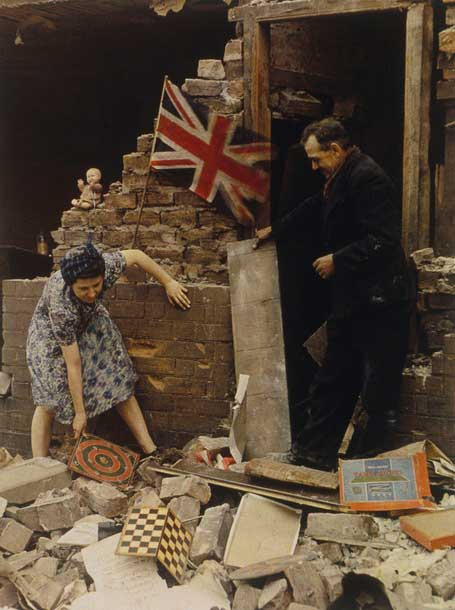 Woman saving board games from bomb wreckage in London. 1939-1945.