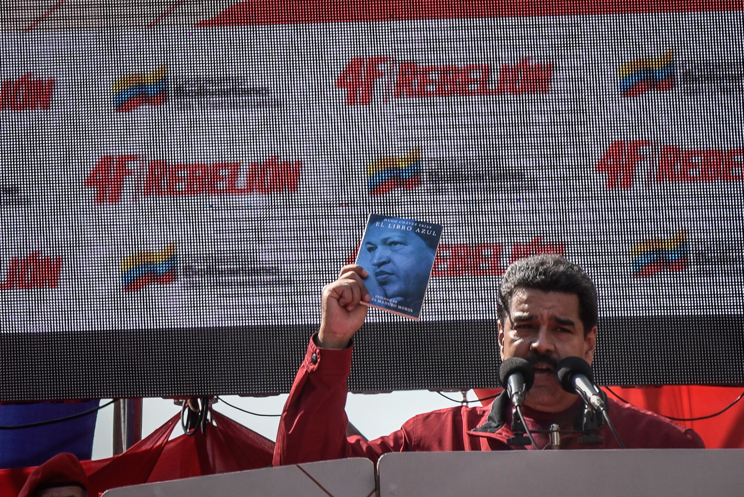 Venezuelan President Nicolás Maduro holds a copy of the El Libro Azul, or The Blue Book, written by his predecessor, Hugo Chávez, while speaking at a rally to commemorate the 24th anniversary of Chávez's failed military coup in Caracas, Venezuela, Feb. 4, 2016.