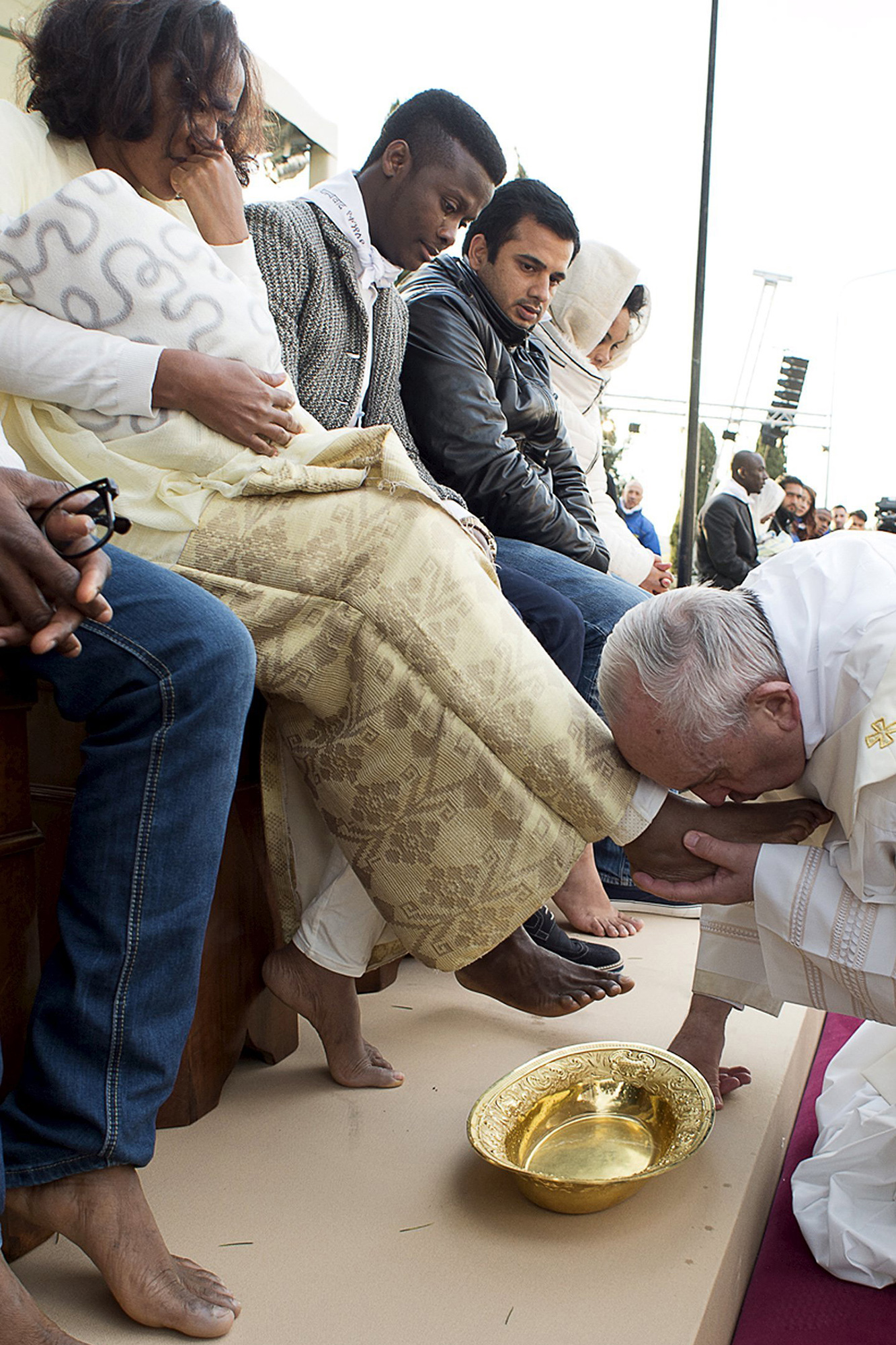 Pope Francis kisses the foot of a refugee during the foot-washing ritual at the Castelnuovo di Porto refugees center near Rome, Italy on March 24, 2016.