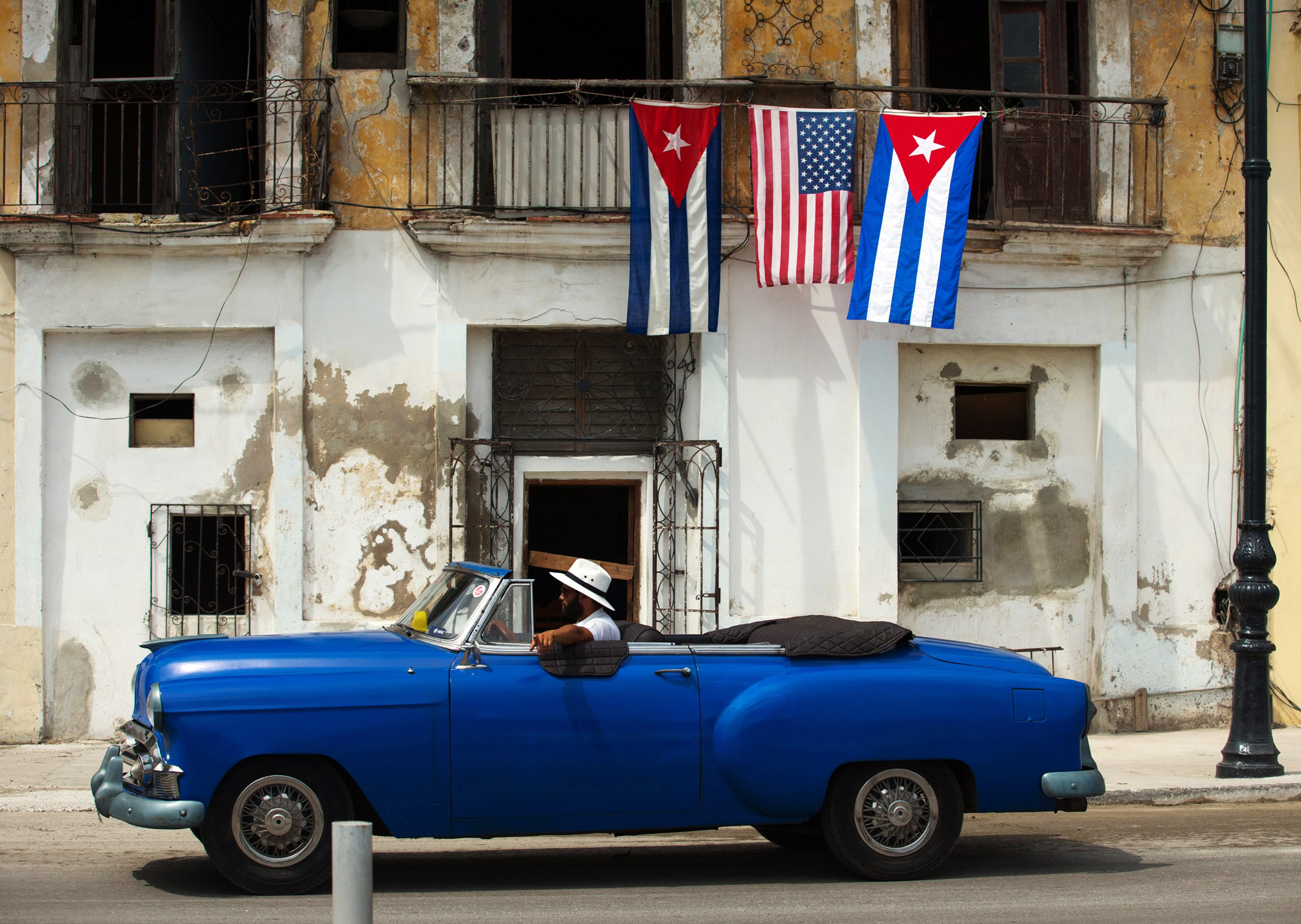 A car passes by a house decorated with the flags of the United States and Cuba in Havana, on March 20 2016.