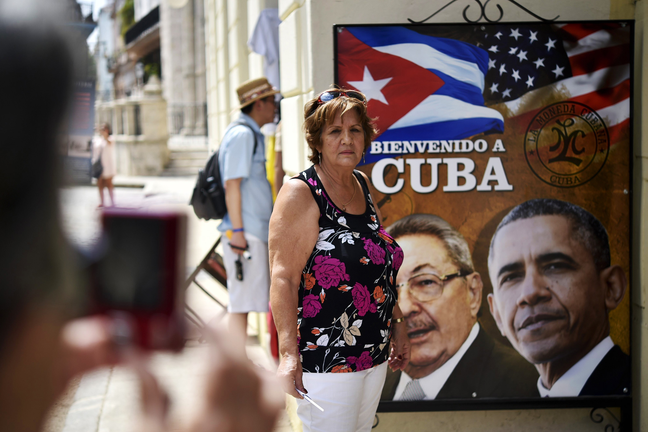 A Cuban woman poses for a picture with a sign displaying images of Cuban and U.S. Presidents Raul Castro and Barack Obama in Havana on March 19, 2016.