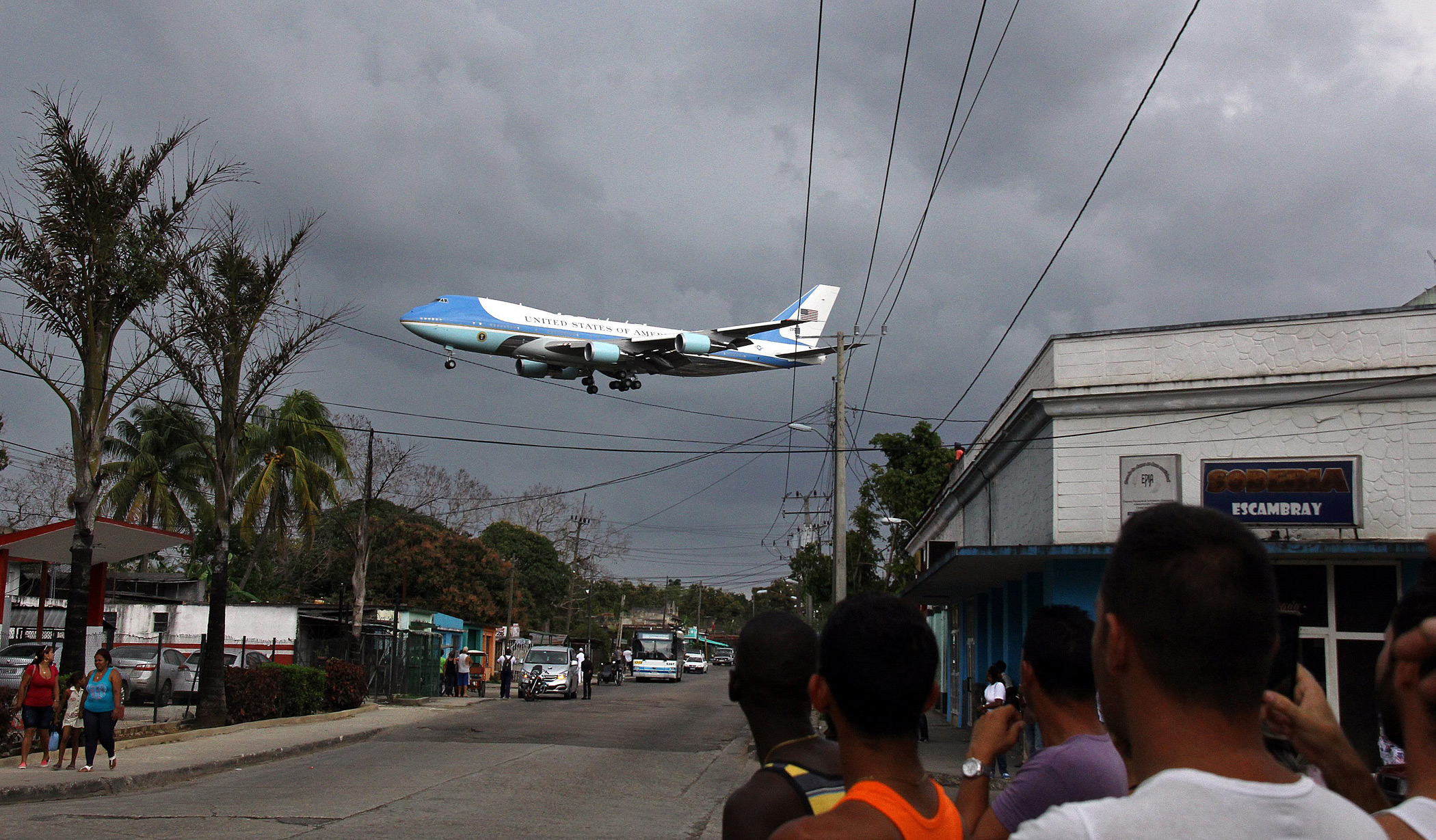 Cuban citizens wacth as Air Force One lands at Jose Marti Airport in Havana on March 20, 2016.