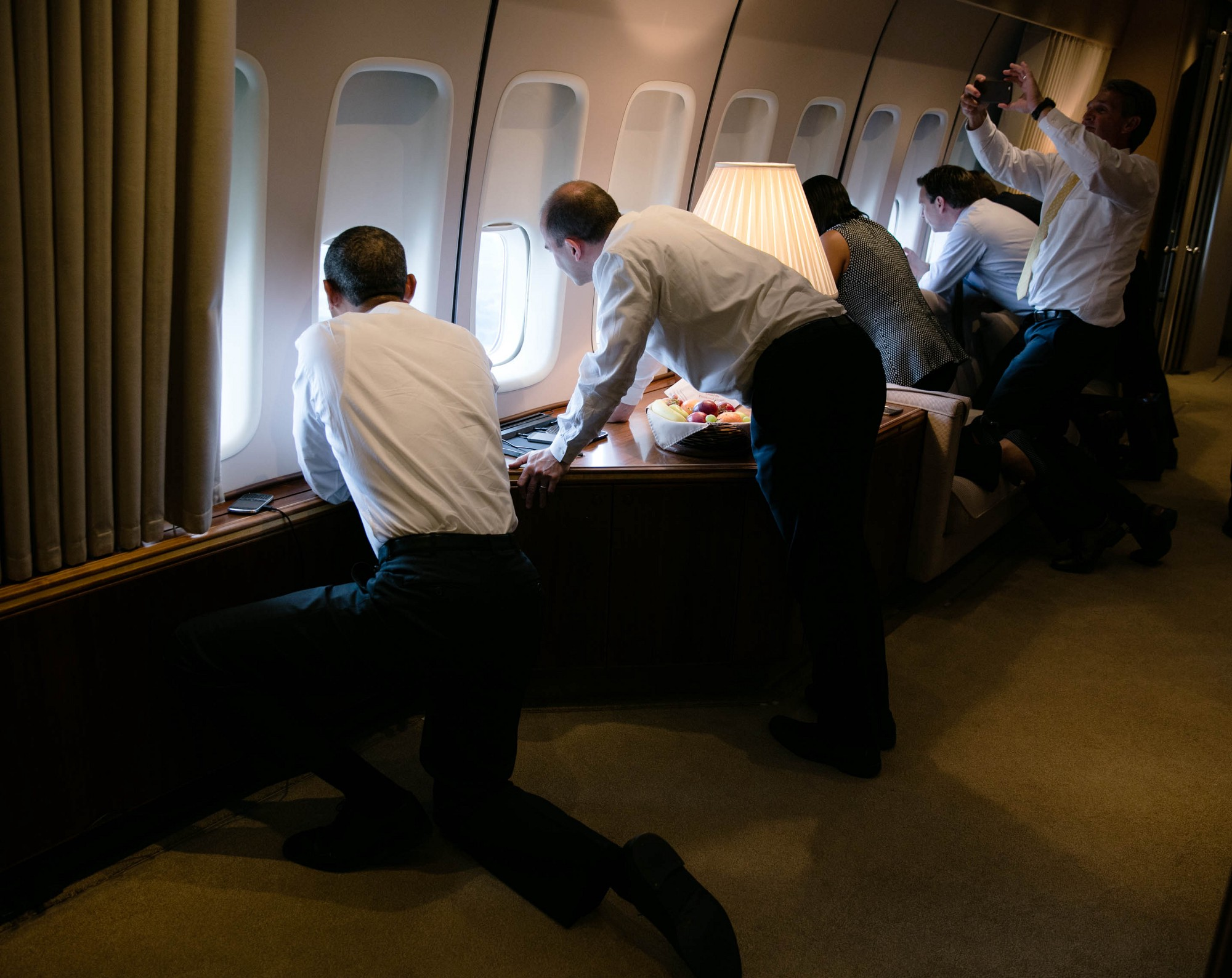 In this photo released by the White House, President Barack Obama joins others in looking out the window of Air Force One on final approach into Havana on March 20, 2016.