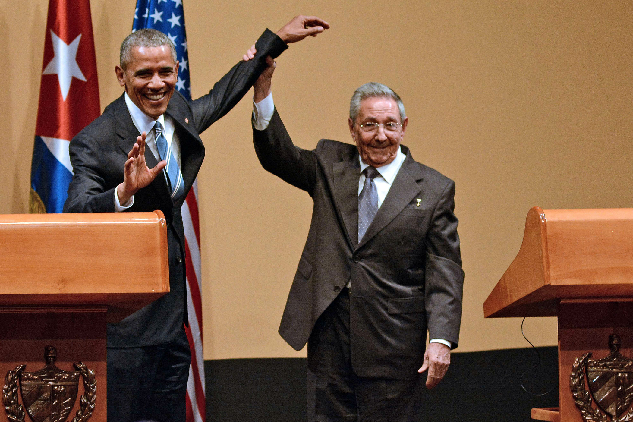 Cuban President Raul Castro, right, raises the hand of U.S. President Barack Obama during a joint press conference at the Revolution Palace in Havana on March 21, 2016.