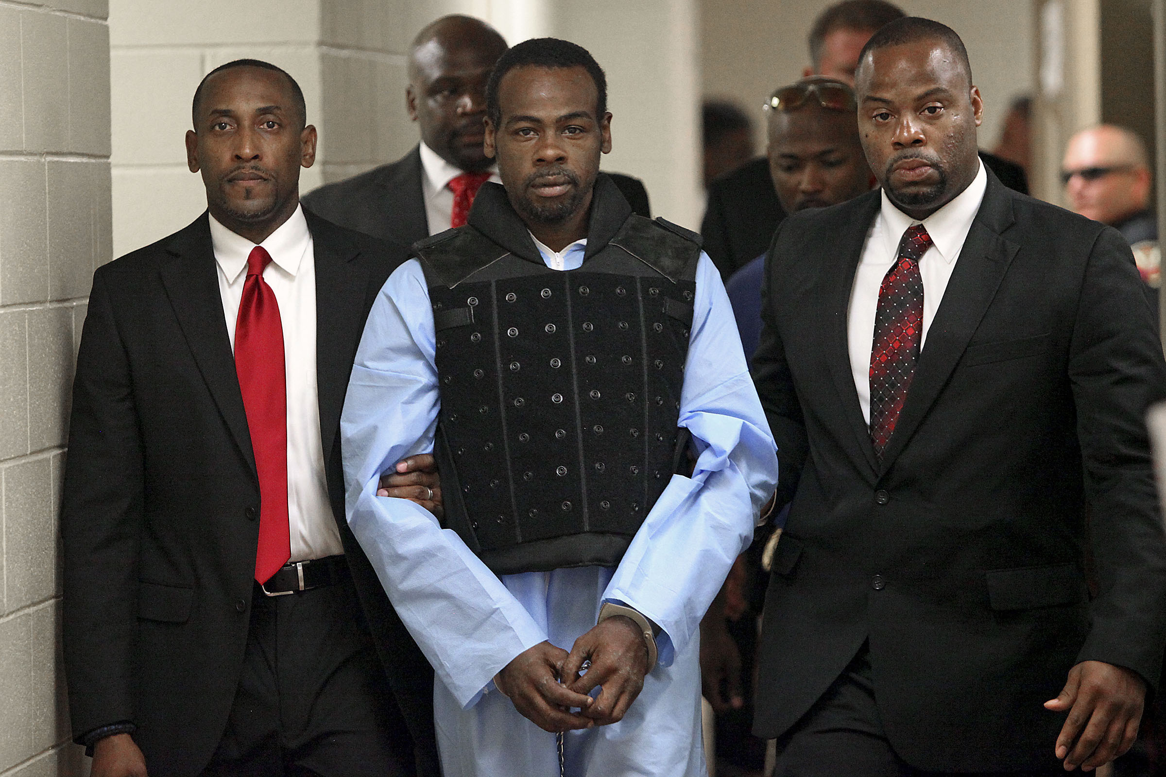 Rafael McCloud is escorted to a holding cell by police investigators in Vicksburg, Miss., on July 1, 2015.