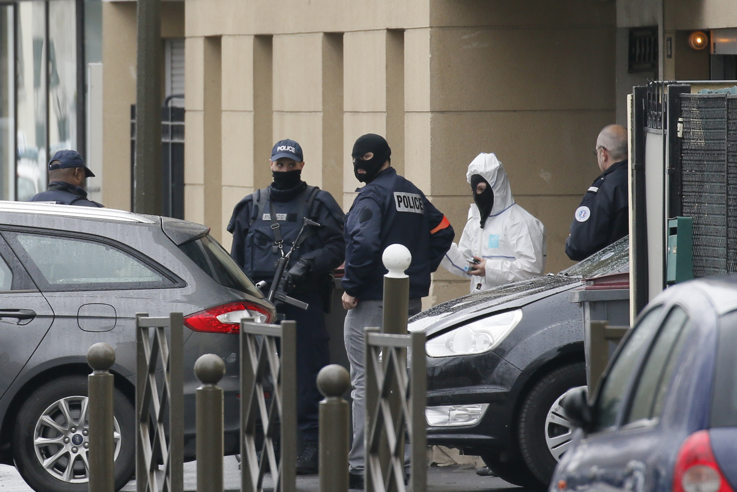 French Police and a forensic expert stand at the entrance of an apartment building after a raid in Argenteuil, a suburb in northern Paris, March 25, 2016.