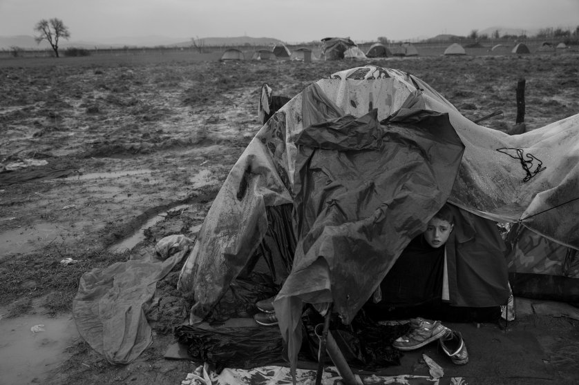 A boy peers out of a tent at a refugee camp in Greece at the Macedonian border, where 12,000 inhabitants—nearly all of them Syrians, Iraqis or Afghans—have been huddling in their shelters atop the mud, March 13, 2016.