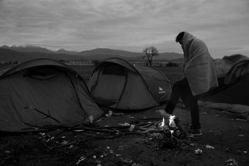 A man warms his feet at a sprawling refugee camp along the border of Greece and Macedonia near the town of Idomeni. The refugees are being stopped from moving beyond Greece and have been languishing in the rain, mud, and cold with insufficient food and medical care while sleeping in small tents, March 12, 2016