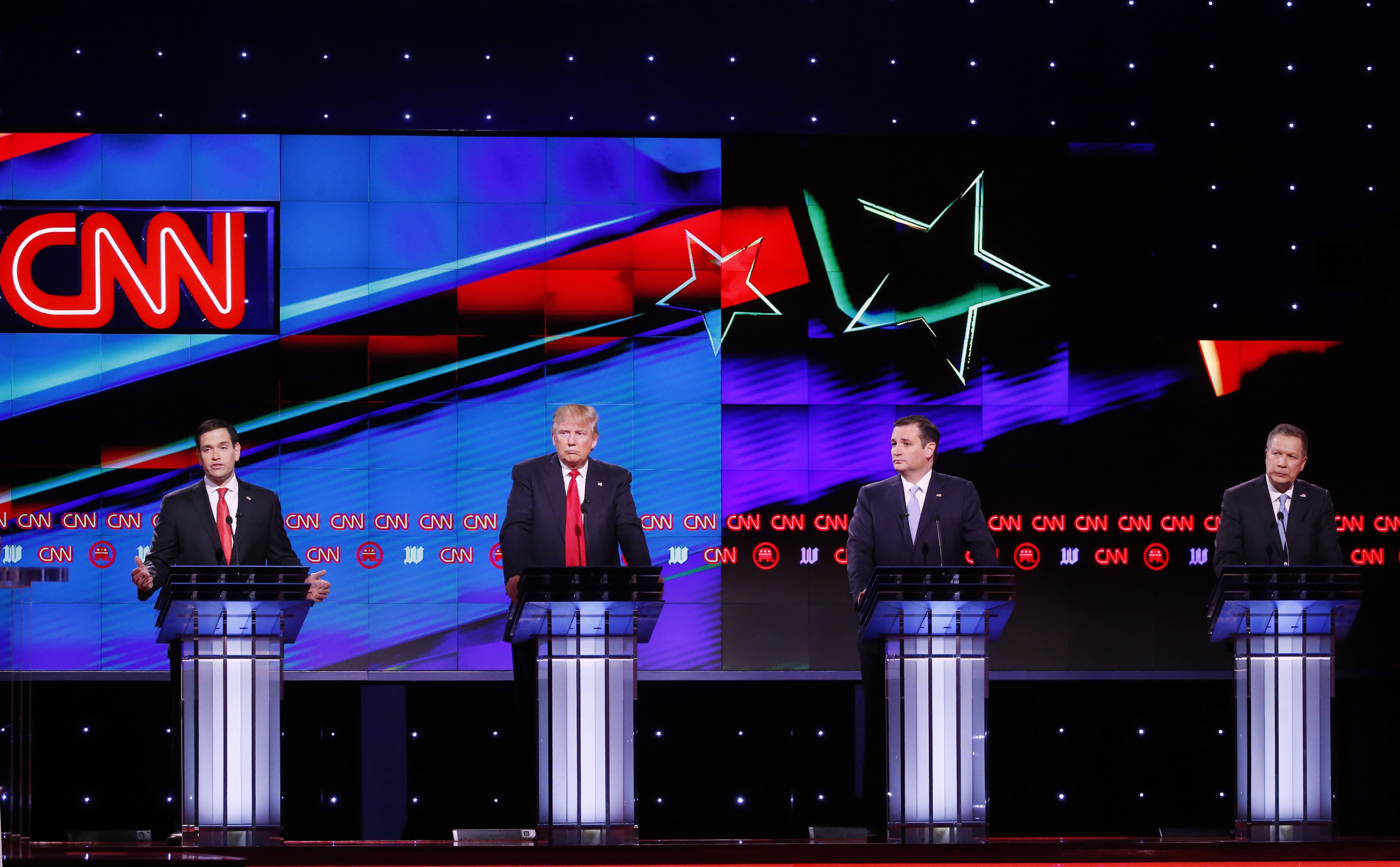 Republican presidential candidate, Sen. Marco Rubio, R-Fla., left, speaks, as Republican presidential candidates, businessman Donald Trump, Sen. Ted Cruz, R-Texas,  and Ohio Gov. John Kasich, listen, during the Republican presidential debate sponsored by CNN, Salem Media Group and the Washington Times at the University of Miami, March 10, 2016, in Coral Gables, Fla.