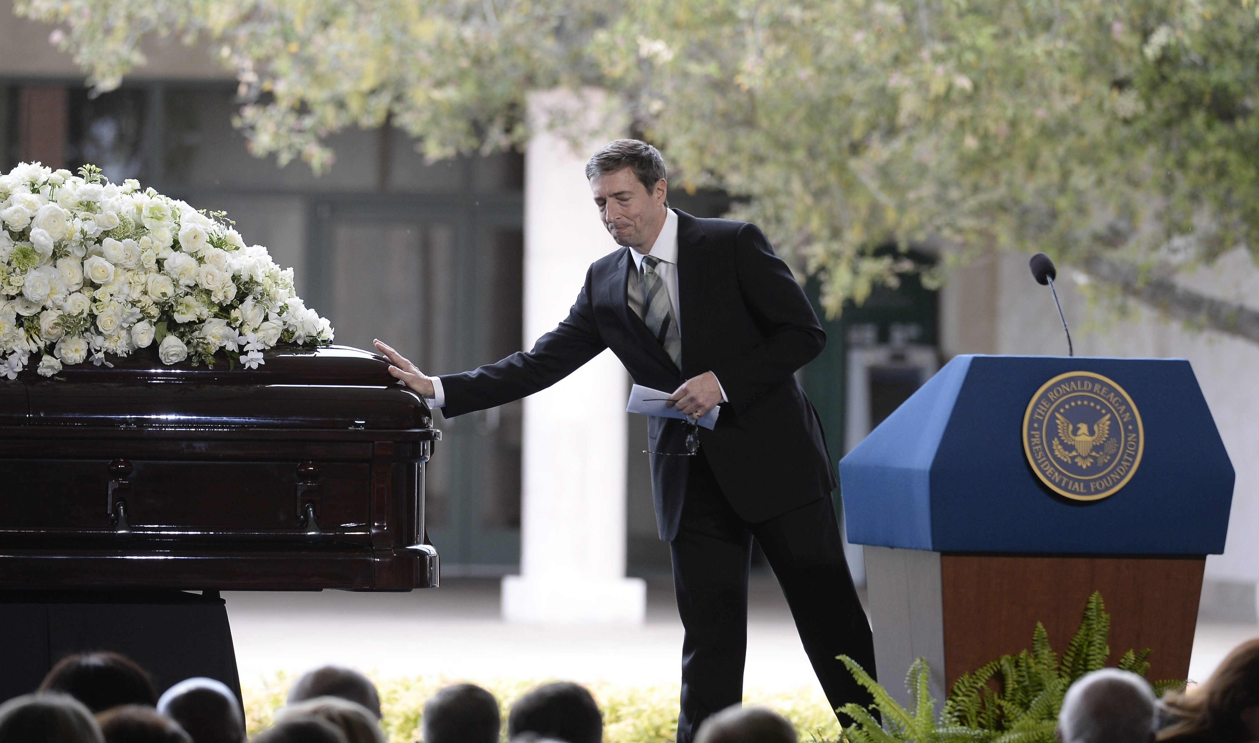 Ronald Reagan Jr touches the casket of his mother during the service, March 11, 2016.