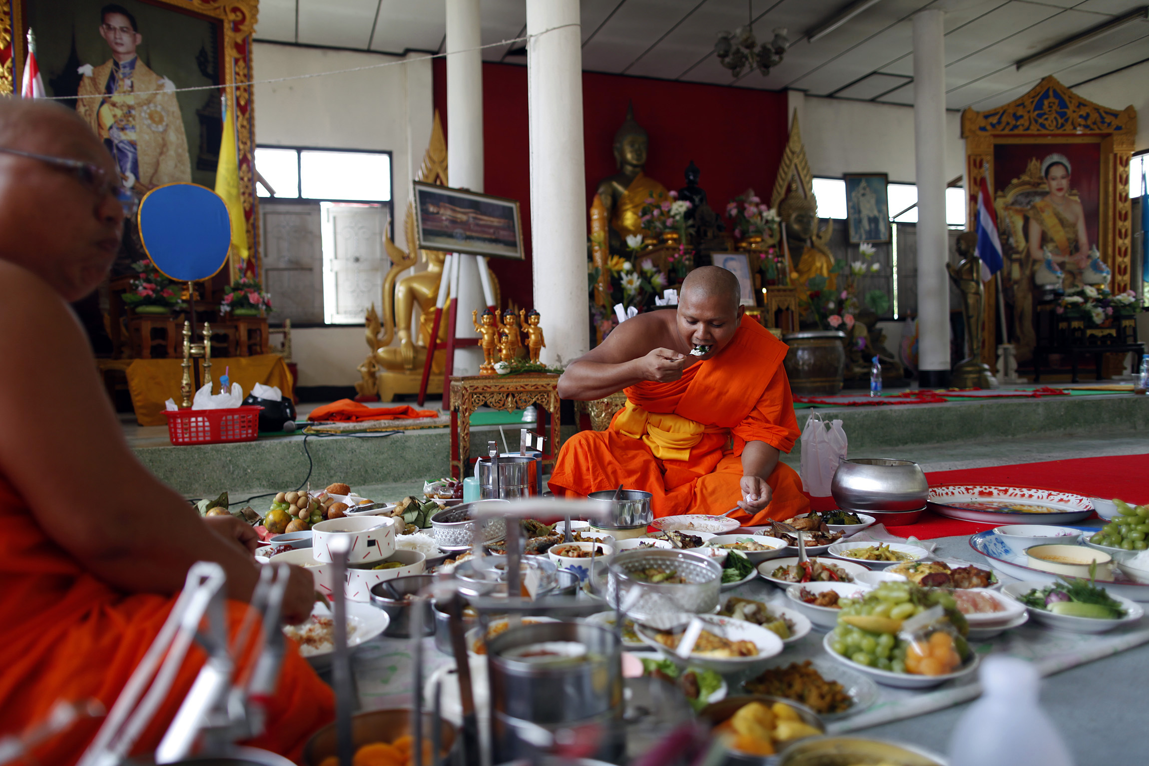 Buddhist monks are offered food during a ceremony at their temple where a Thai army unit is also based in the troubled Yala province in southern Thailand on March 31, 2010