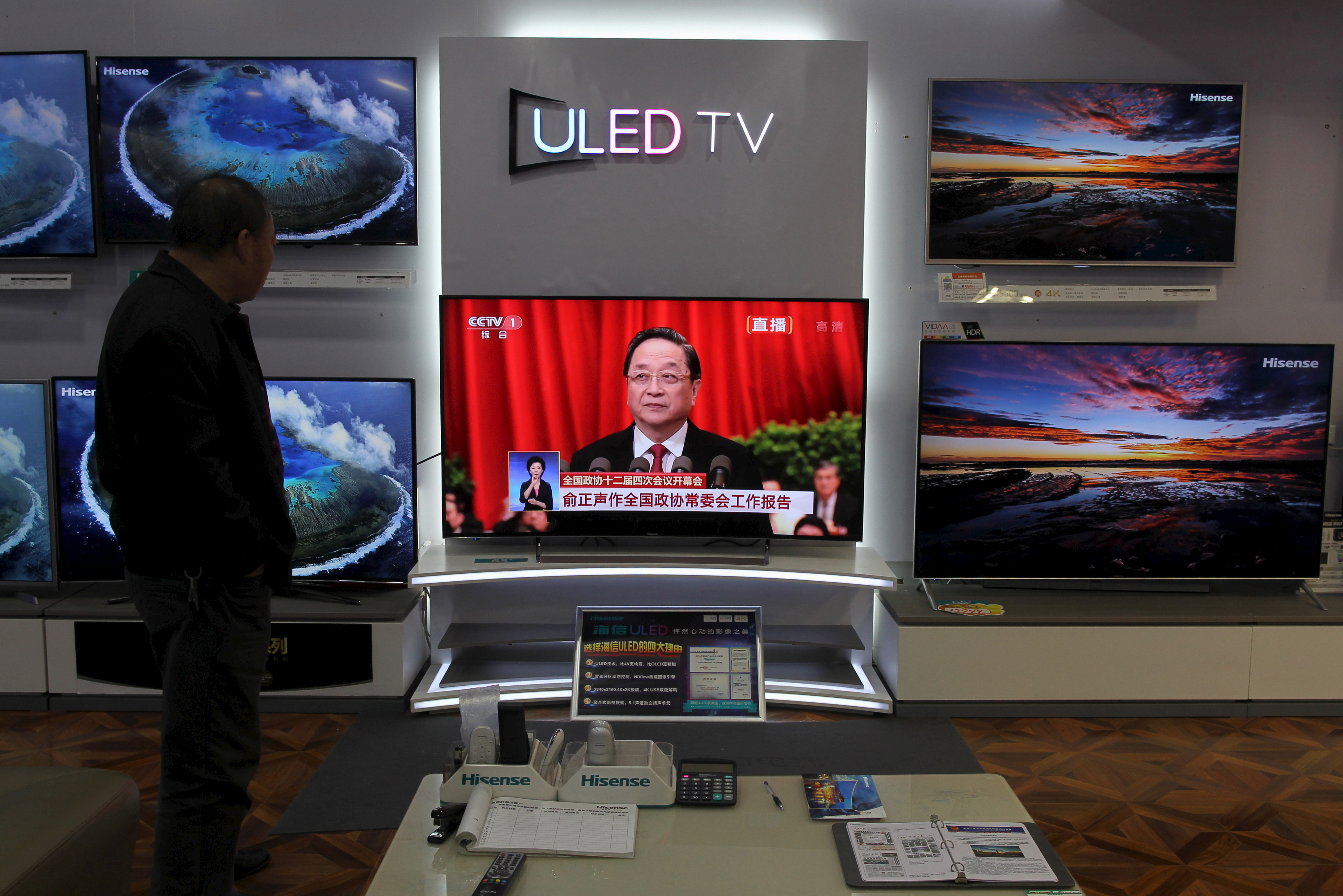 A man watches a TV screen showing live broadcast of Yu Zhengsheng, chairman of the National Committee of the Chinese People's Political Consultative Conference (CPPCC), giving a speech during the opening session of the CPPCC, at a shopping mall in Kunming, the Chinese province of Yunnan, on March 3, 2016