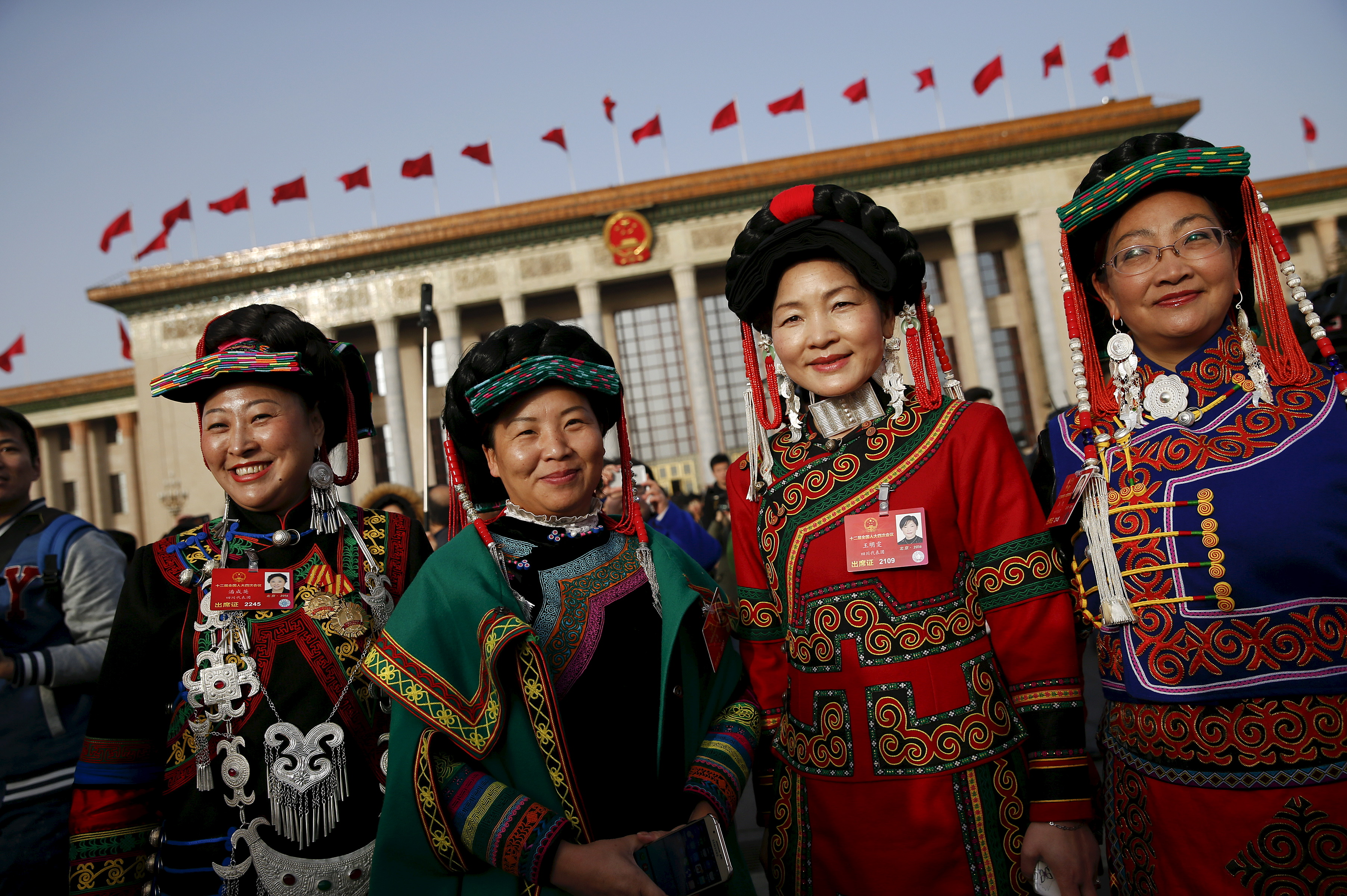 Ethnic minority delegates pose for pictures outside the Great Hall of the People ahead of the opening session of the National People's Congress in Beijing on March 5, 2016